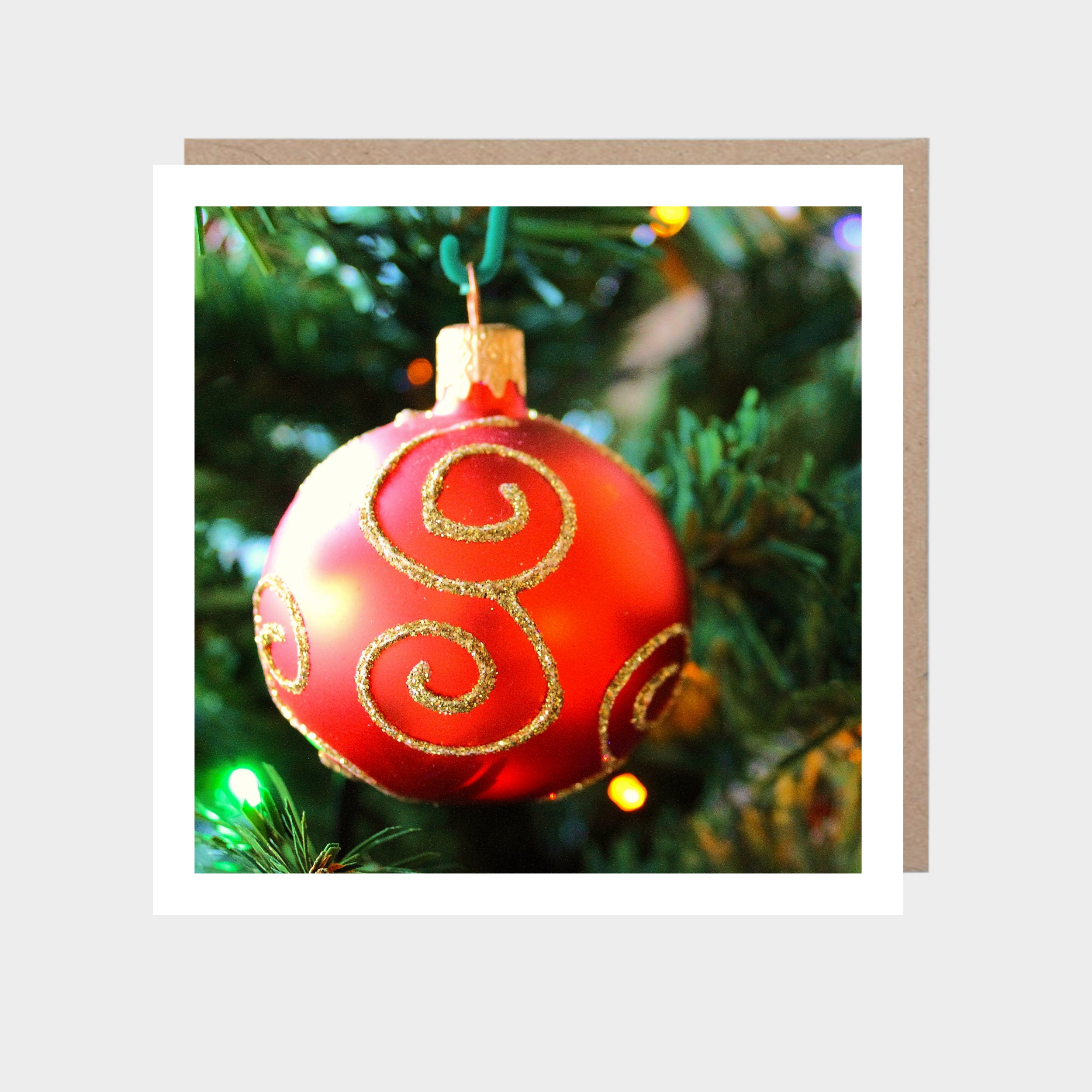 Square card with a close-up photo of a red and gold bauble, with a brown kraft envelope