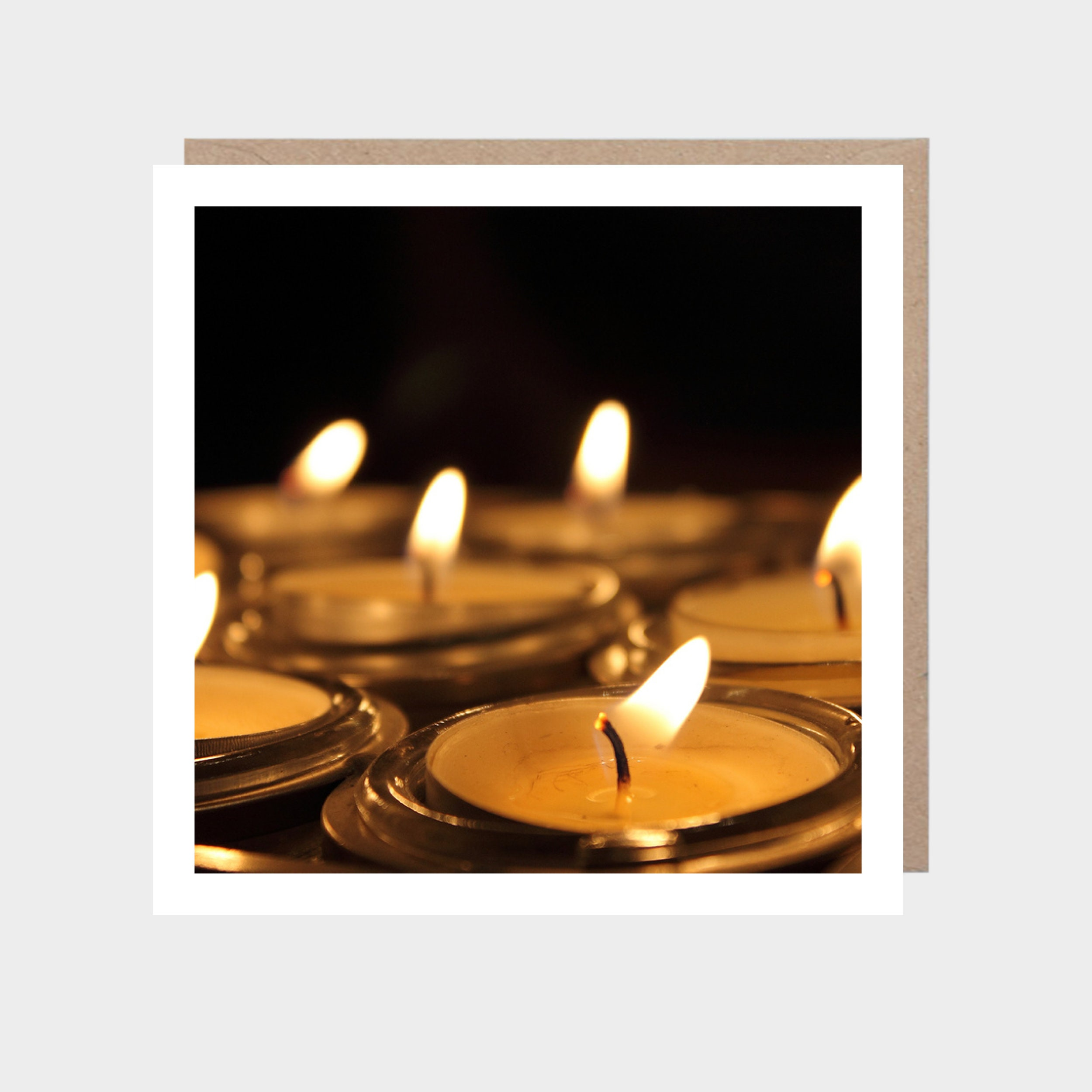 Square card with a close-up photo of lit tealight flames, with a brown kraft envelope