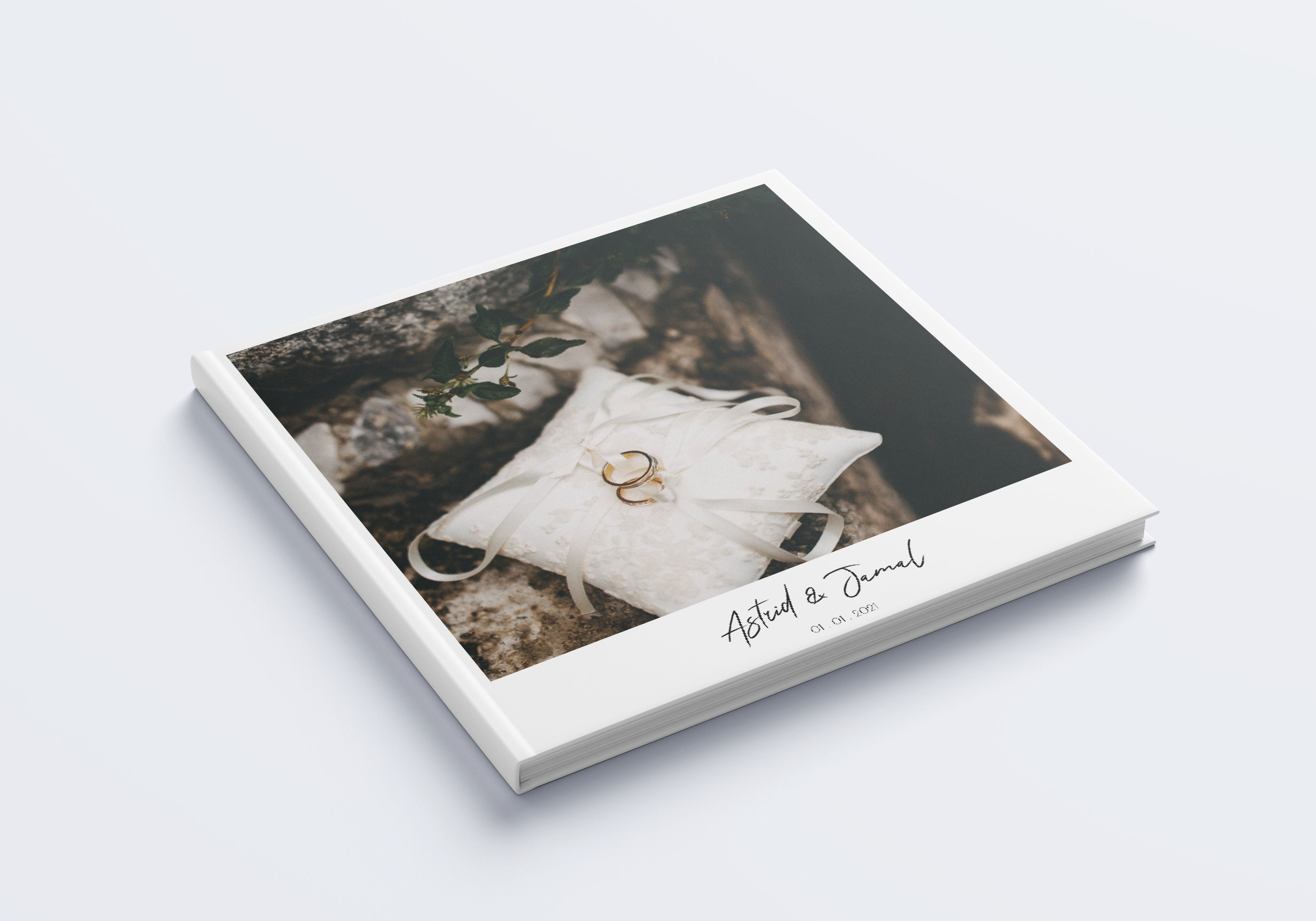A photograph of a square hardcover book, with a wedding photo printed on the front cover. There is some text underneath the image, on a white background, with the couples names and wedding date.