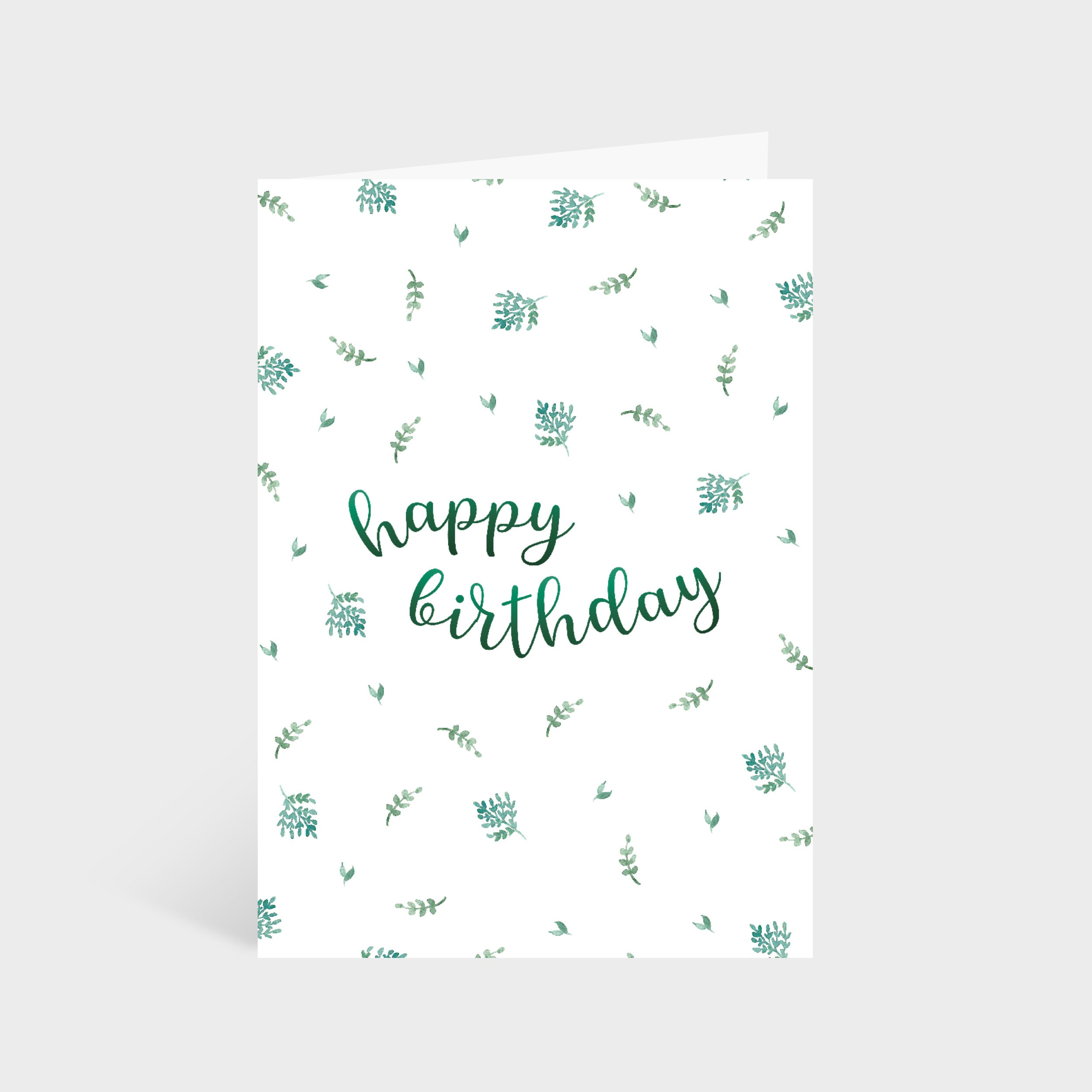 """Standing white card with a green leafy pattern. Text in the centre of the card says """"Happy Birthday"""""""
