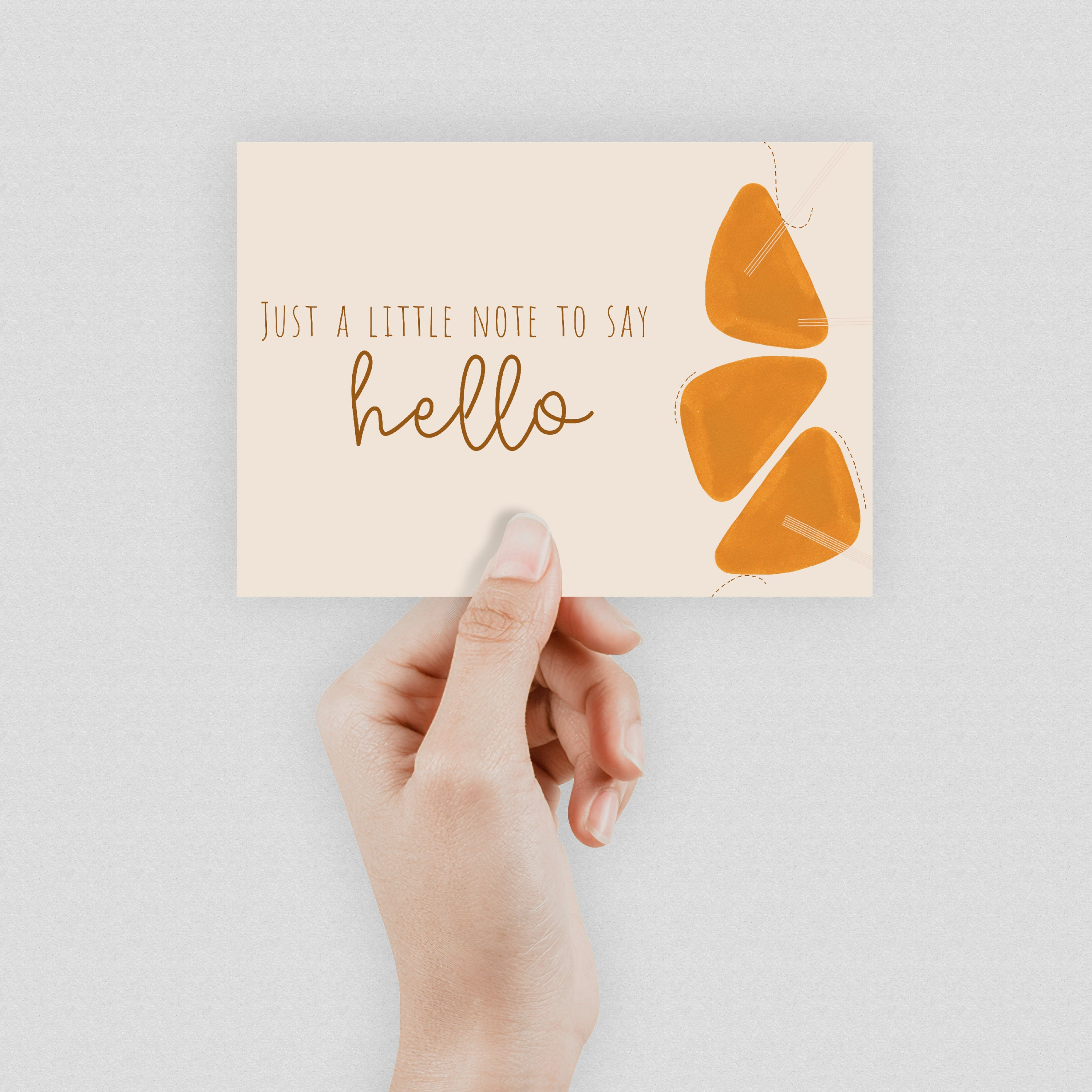 """A hand holding a cream postcard which says """"Just a little note to say hello""""."""