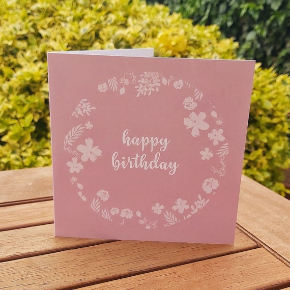 Photograph of a square pink card with an illustrated white floral circle and 'happy birthday' in the middle of the card. The card is sat on a wooden table outside in the sun.