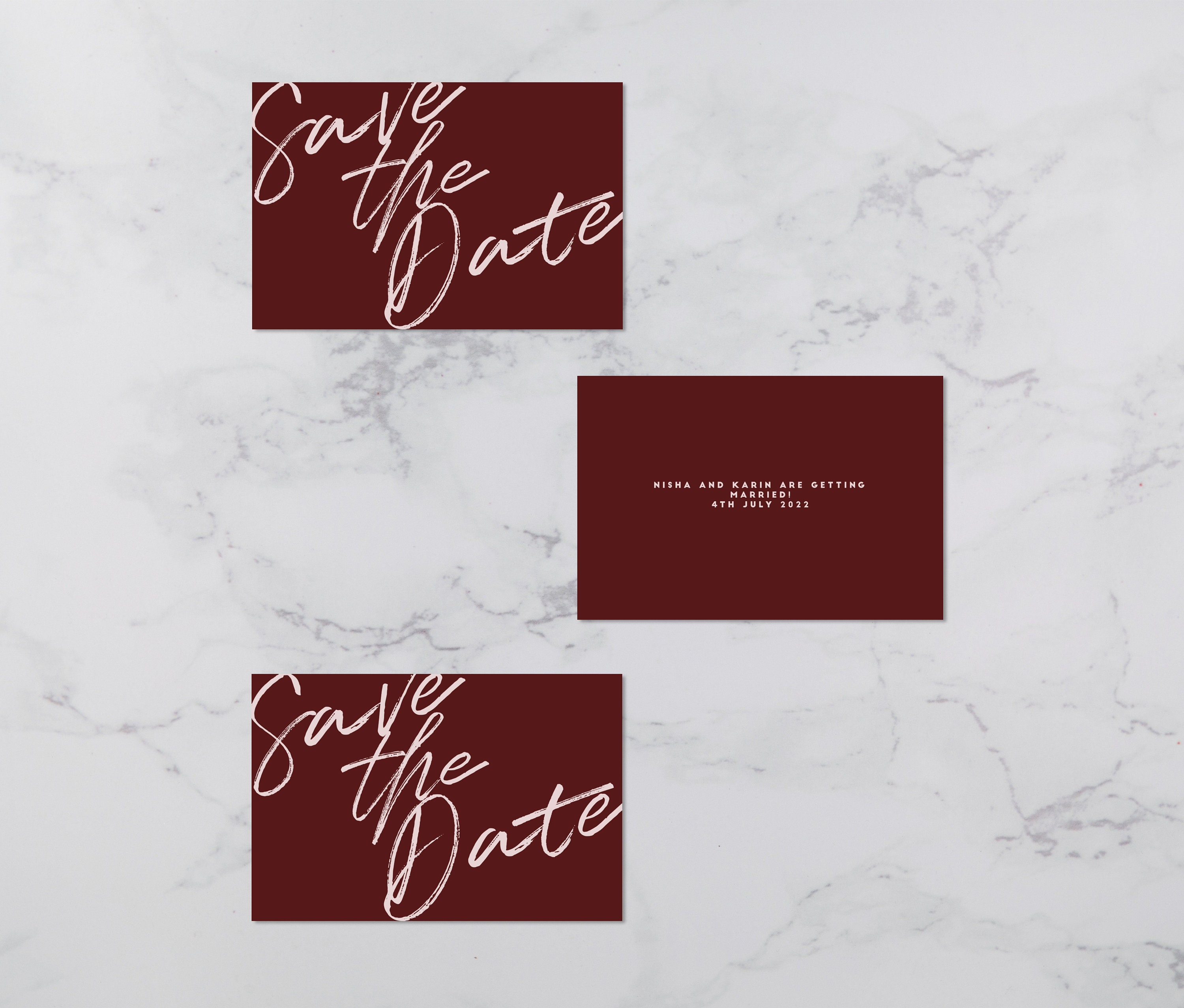 Flat lay photograph showing 3 wedding save the date cards (some front-facing, some showing the reverse). Each card is burgundy