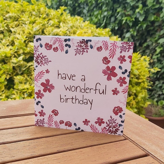 Photograph of a square pink card with illustrated burgundy and navy flowers around the edge. The card is standing on a wooden table with greenery behind.