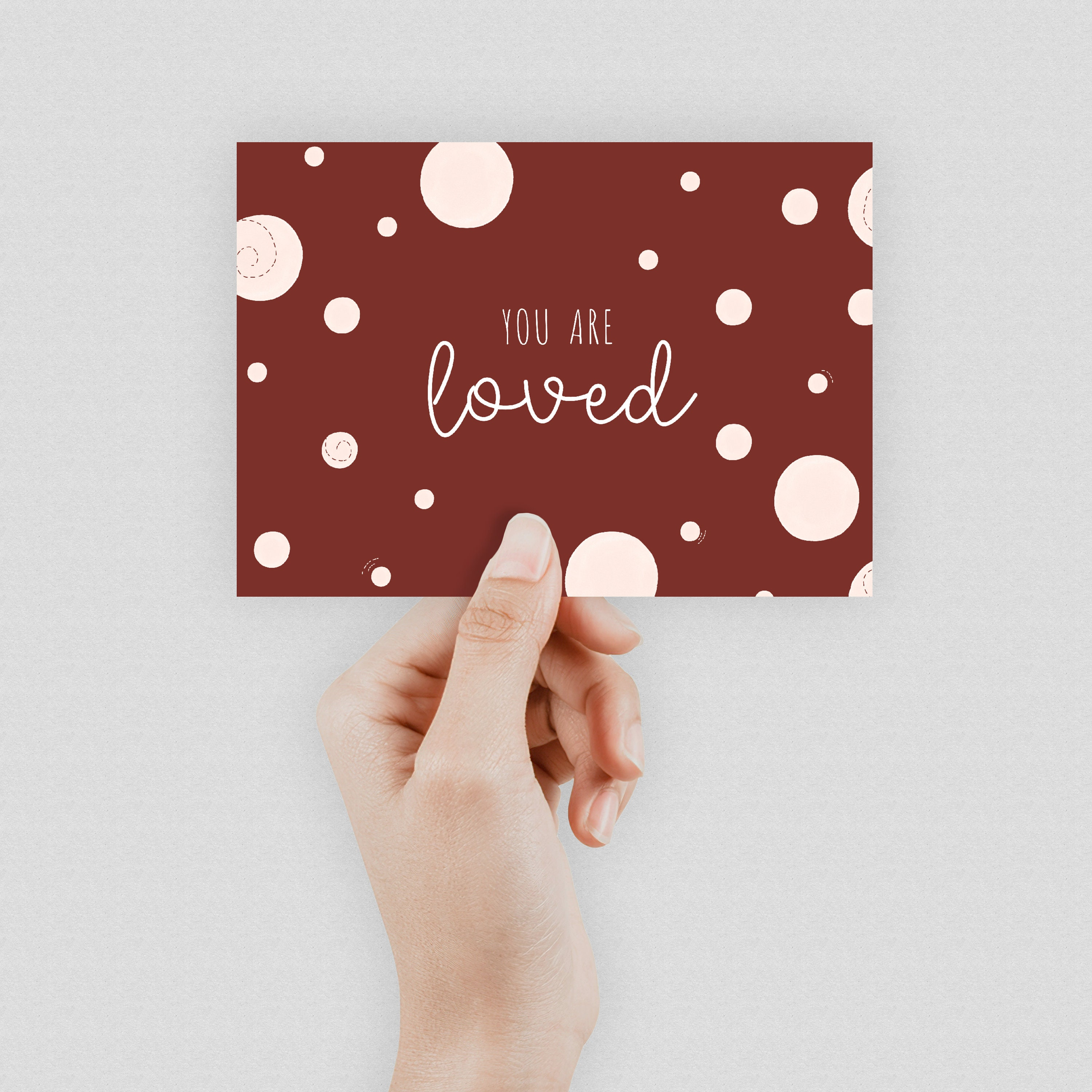 """A hand holding a bright burgundy postcard which says """"You are loved"""" in the middle"""