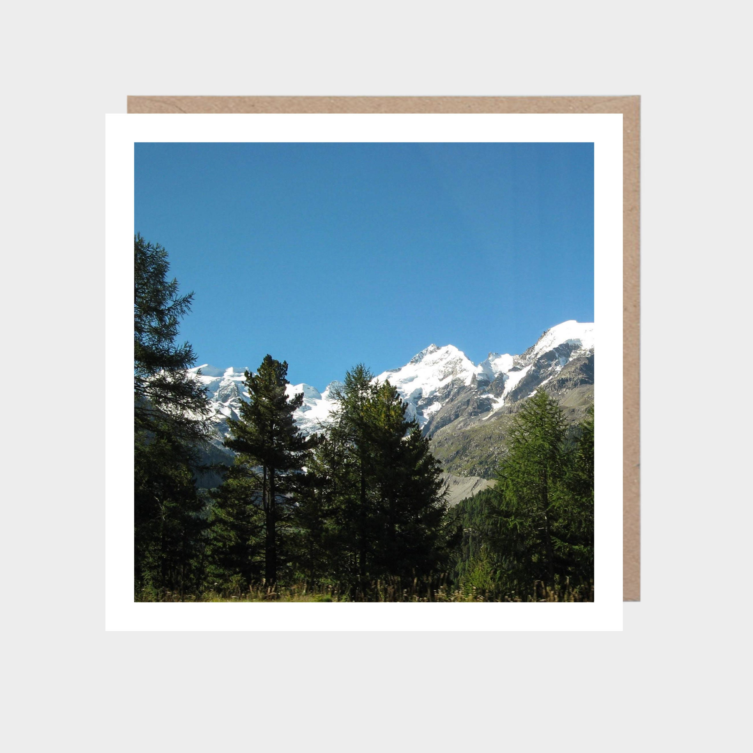 Square card with a photo of The Alps, with a brown kraft envelope