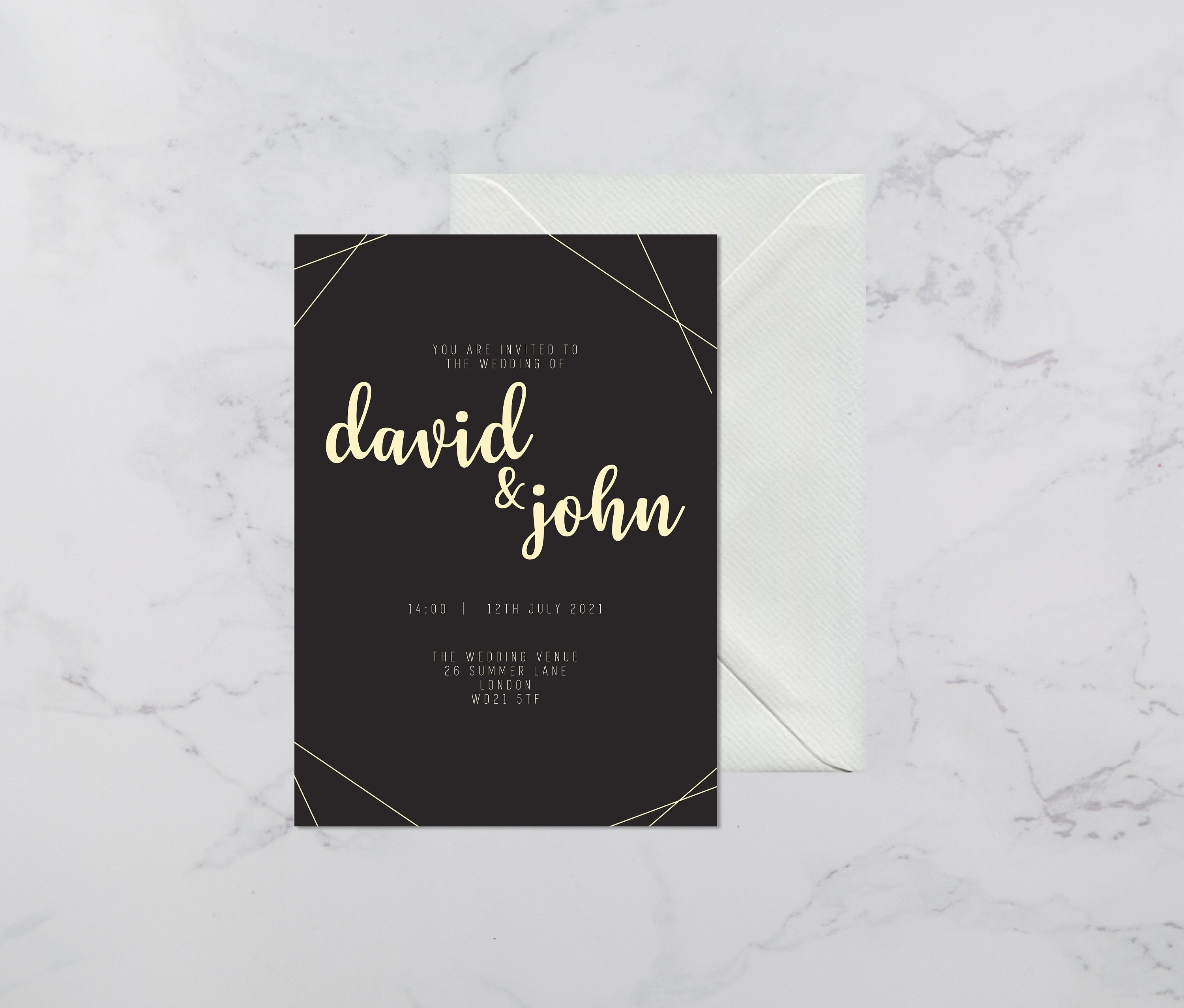 Flat lay photograph of a wedding invitation and white envelope. The design of each is mostly black card with gold colour details.