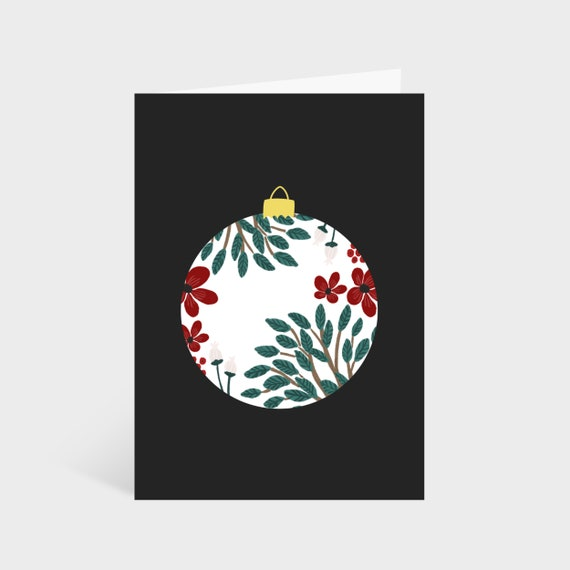 Standing black card with illustrated white and floral bauble in the centre.