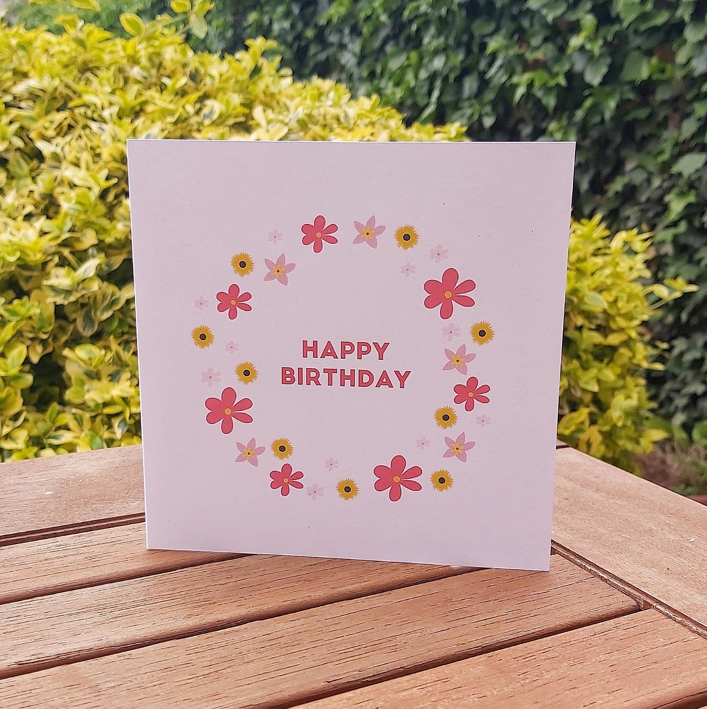 Photograph of a square light pink card with a circle of bright pink and yellow flowers, and the words 'Happy Birthday' in the middle. The card is standing on a wooden table in the sunshine
