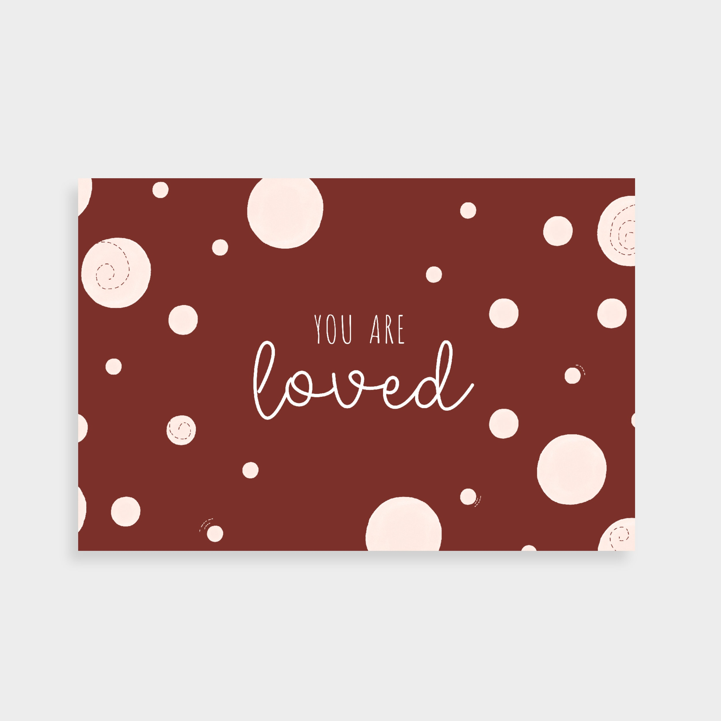 """Dark burgundy postcard with light pink dots. Postcard says """"You are loved"""" in the middle"""