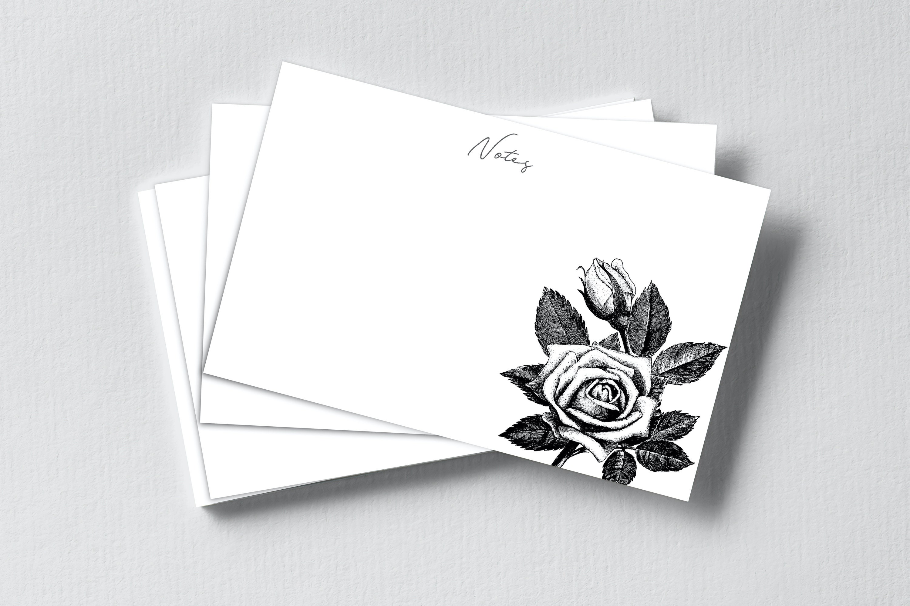 A stack of notecards with a black and white illustration of a rose on each.
