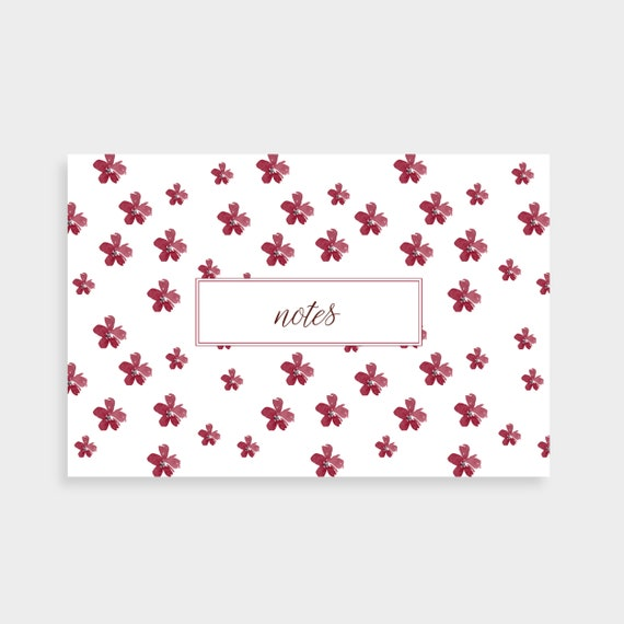 "A white notecard with a pattern of larger red flowers. Notecard says ""Notes"" in a red outlined box in the centre"