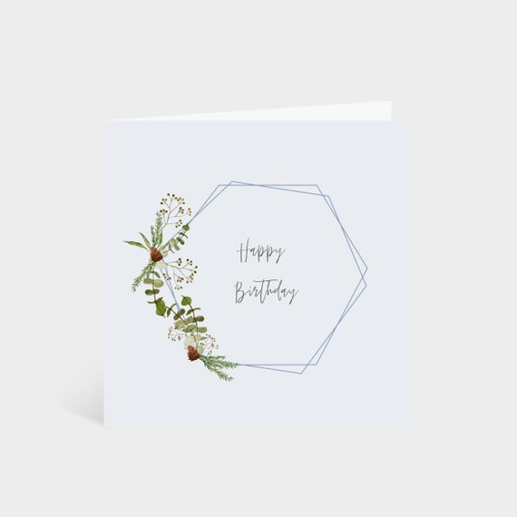 Standing square light blue card with a gold hexagon, edged with wintery leaves, eucalyptus and pine cones, and the words 'Happy Birthday' in the middle