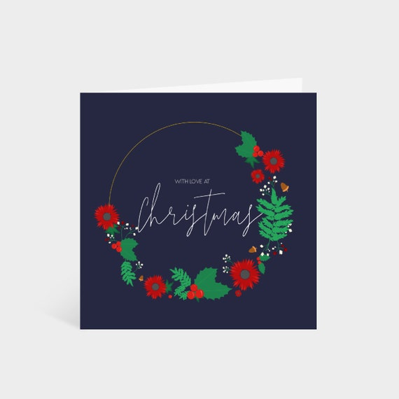 """Standing dark blue square card with an illustrated Christmas wreath; says """"With love at Christmas"""" in a calligraphy font in the middle"""
