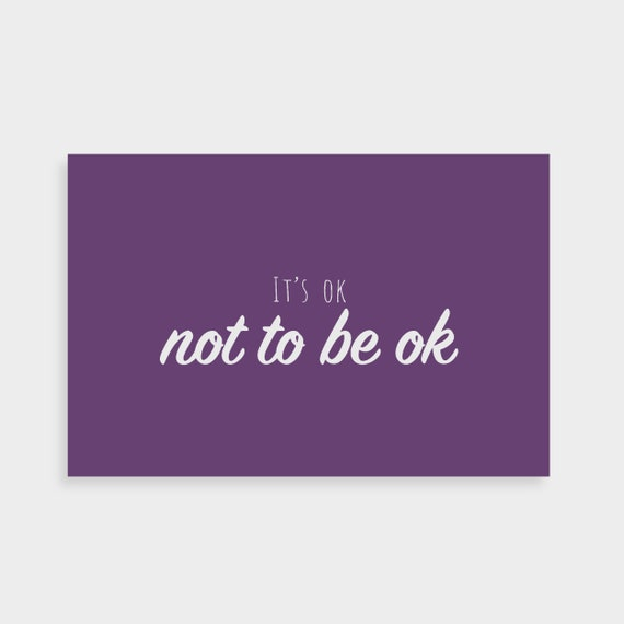 """Purple postcard which says """"It's ok not to be ok"""" in a white calligraphy font in the middle"""