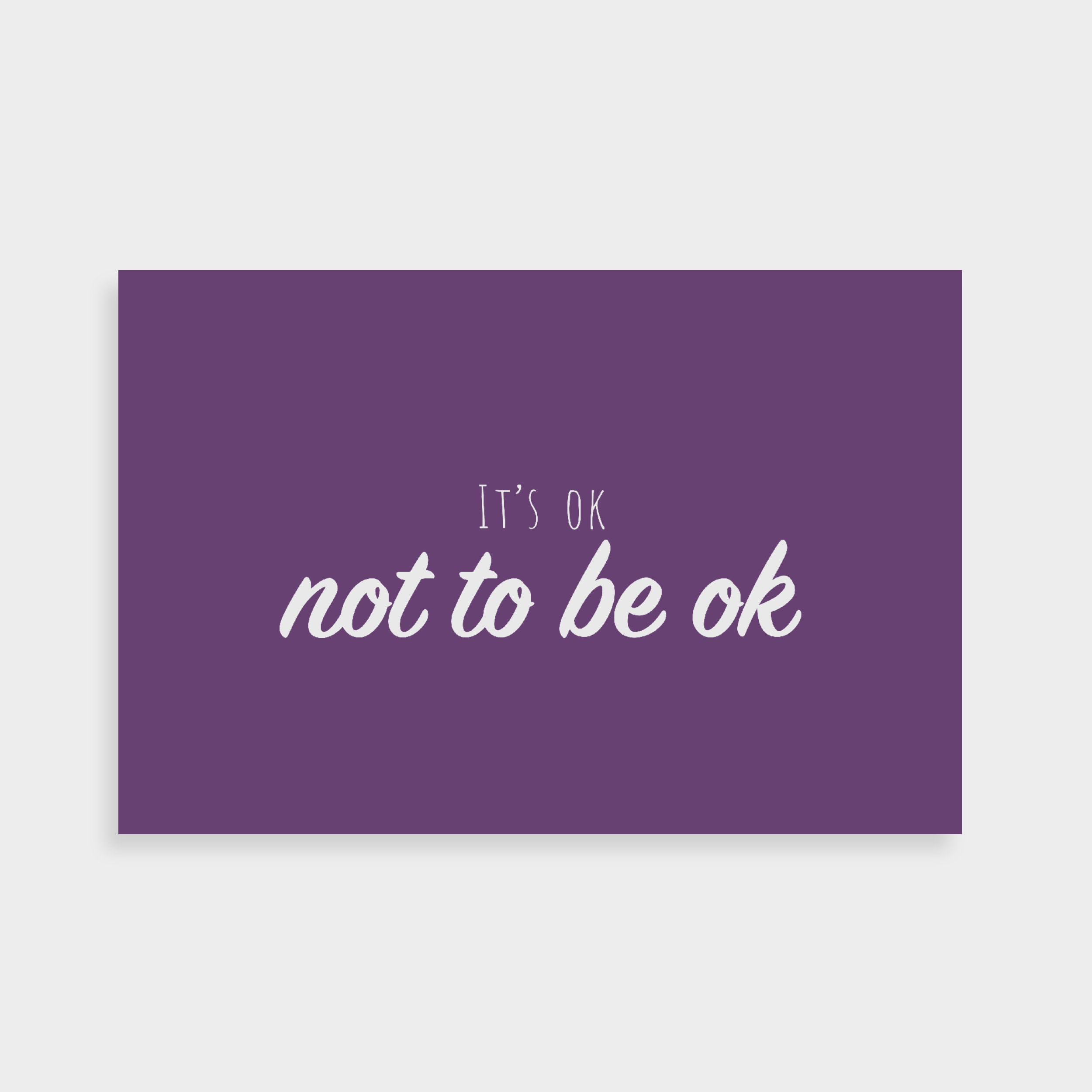 "Purple postcard which says ""It's ok not to be ok"" in a white calligraphy font in the middle"