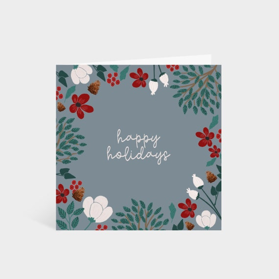 Standing square blue-grey card with a border of winter foliage and flowers, and the words 'Happy Holidays' in the centre