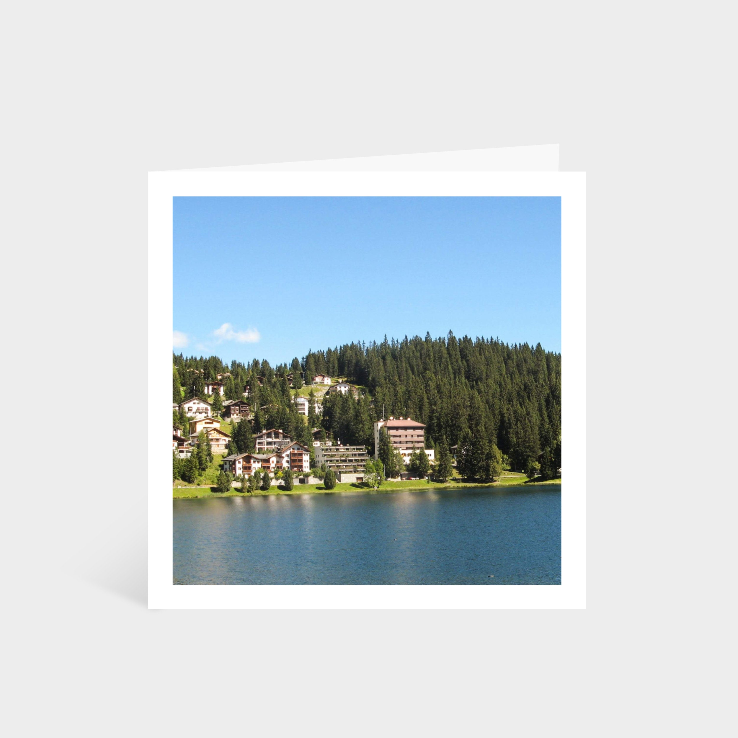 Standing square card with a photo of a green Switzerland landscape with houses overlooking a lake