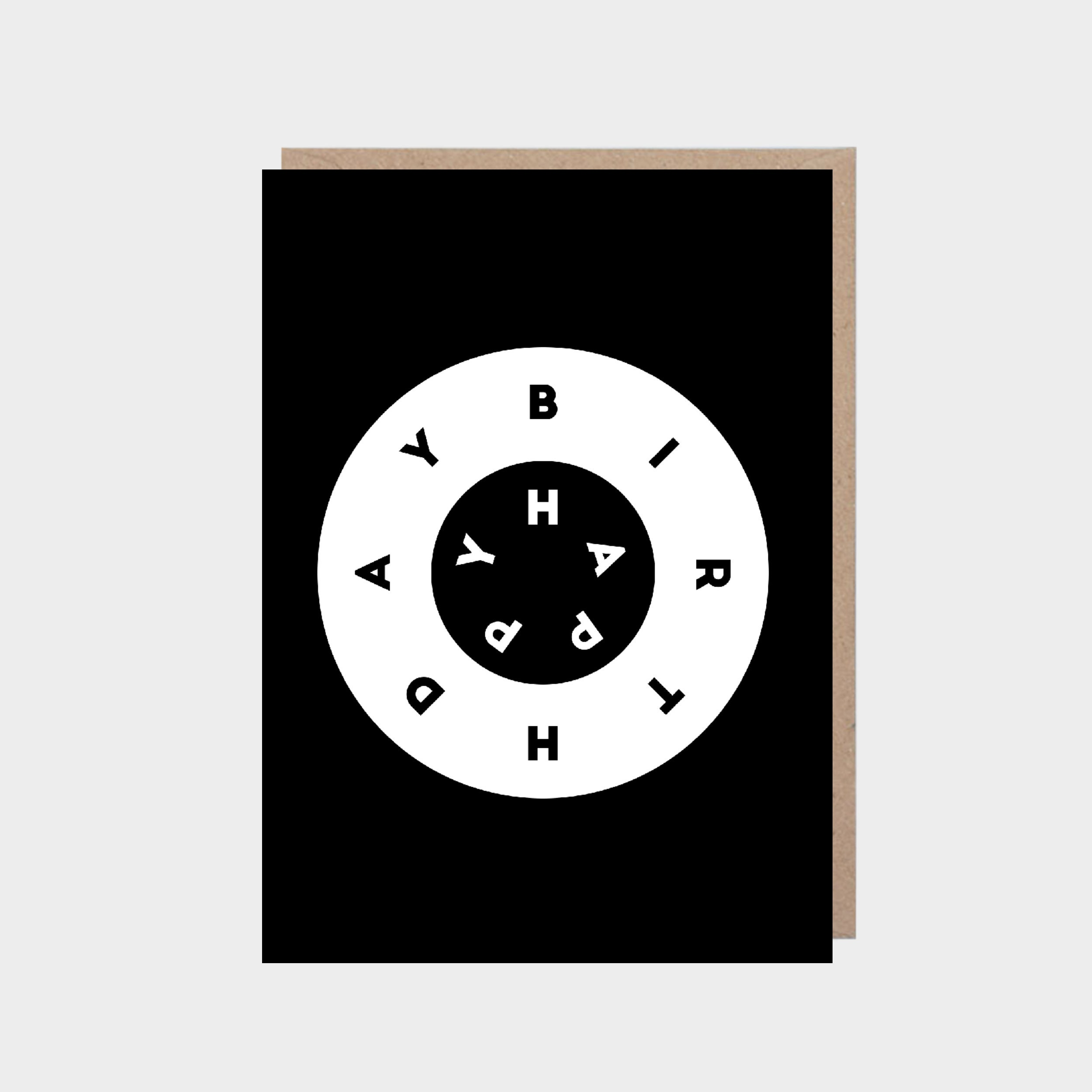 Standing black card with black and white rings in the centre, with a brown kraft envelope.