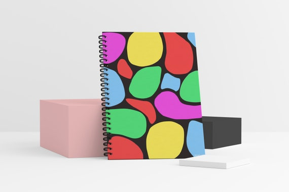 A standing spiral-bound notebook with a rainbow shapes design on the front cover