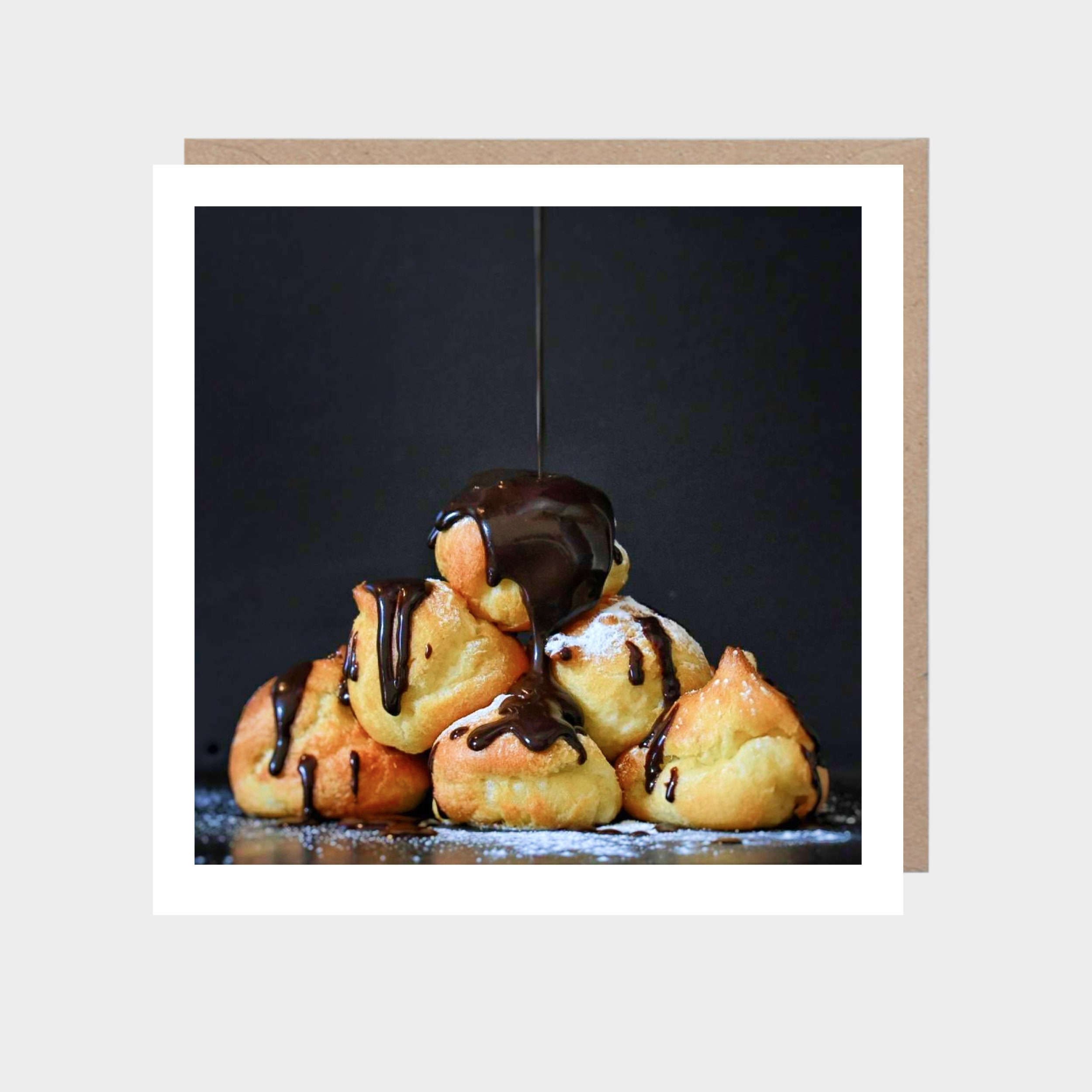 Square card with a close-up photo of profiteroles, with a brown kraft envelope