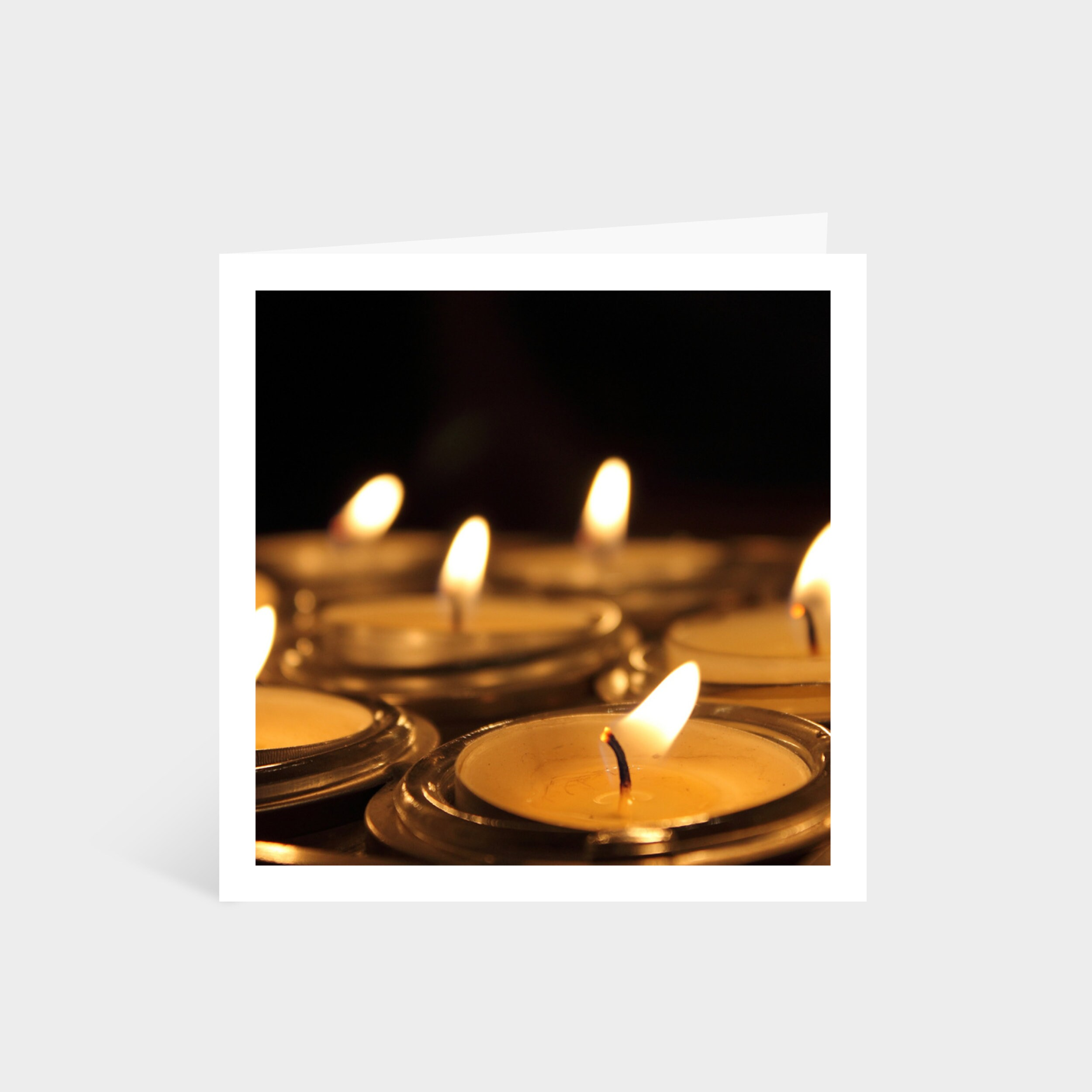 Standing square card with a close-up photo of a set of lit tealights