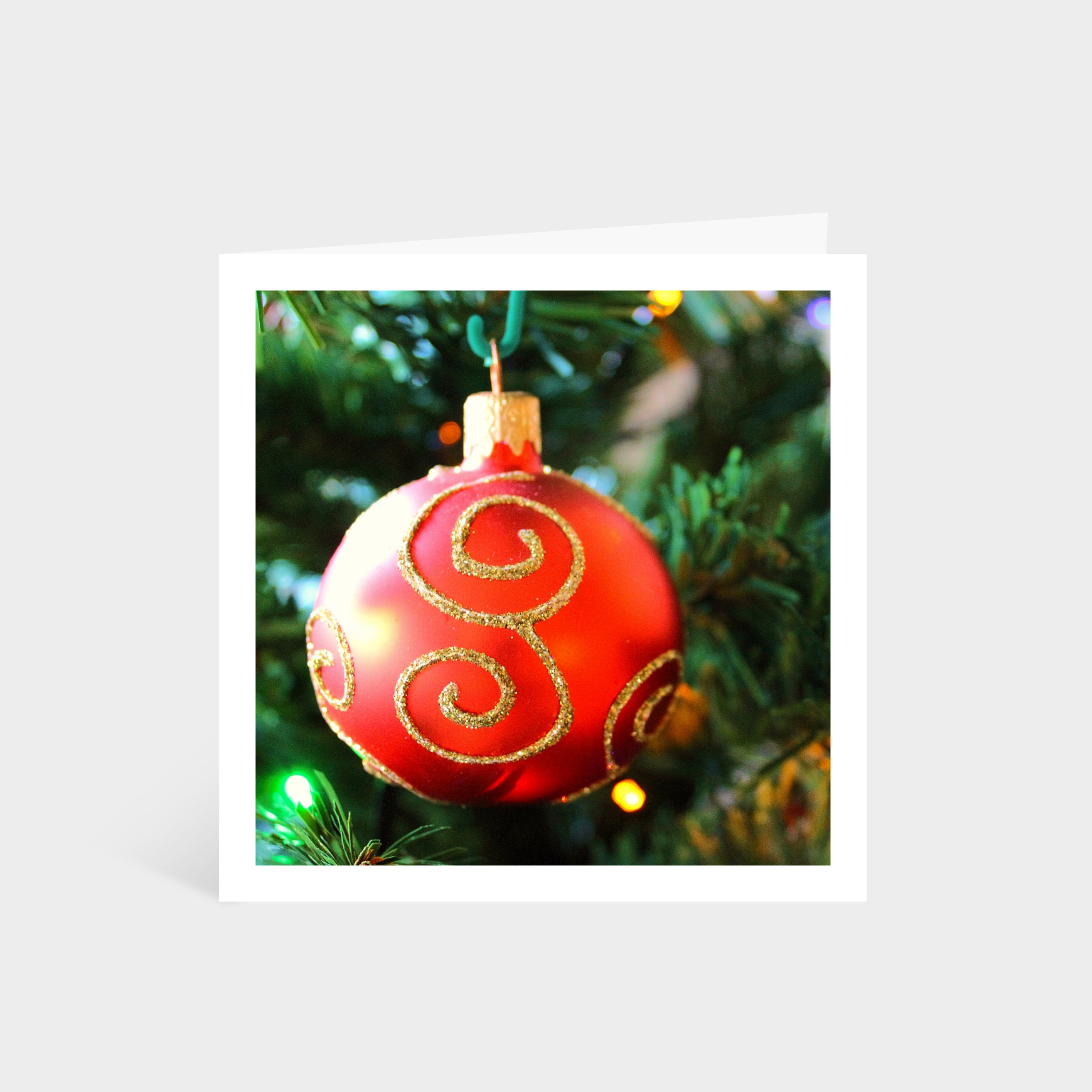 Standing square card with a close-up photo of a red and gold bauble hanging on a Christmas tree