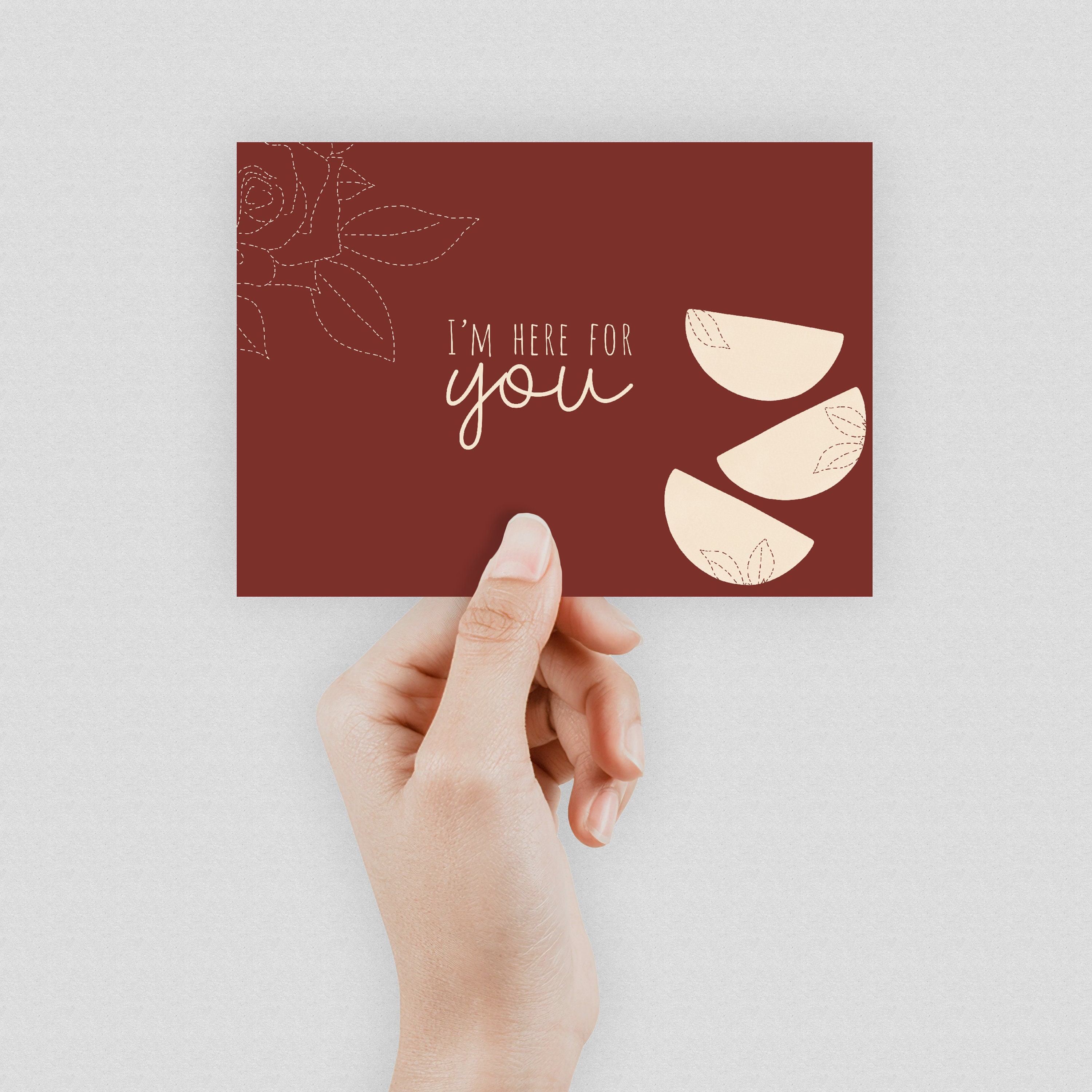 """A hand holding a burgundy postcard which says Here for you"""" in the middle."""