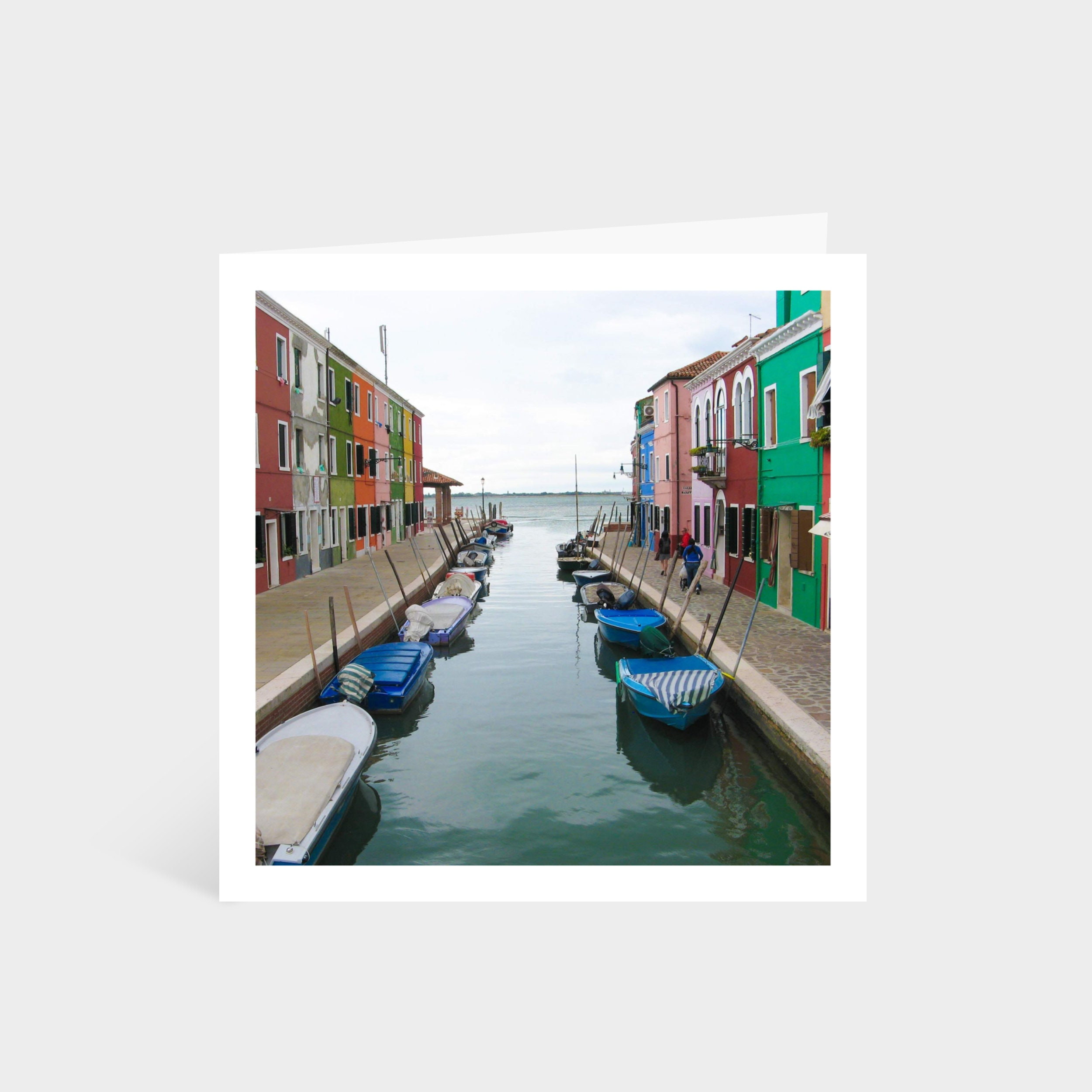 Standing square card with a photo looking down a canal street in Burano, with a rainbow of houses