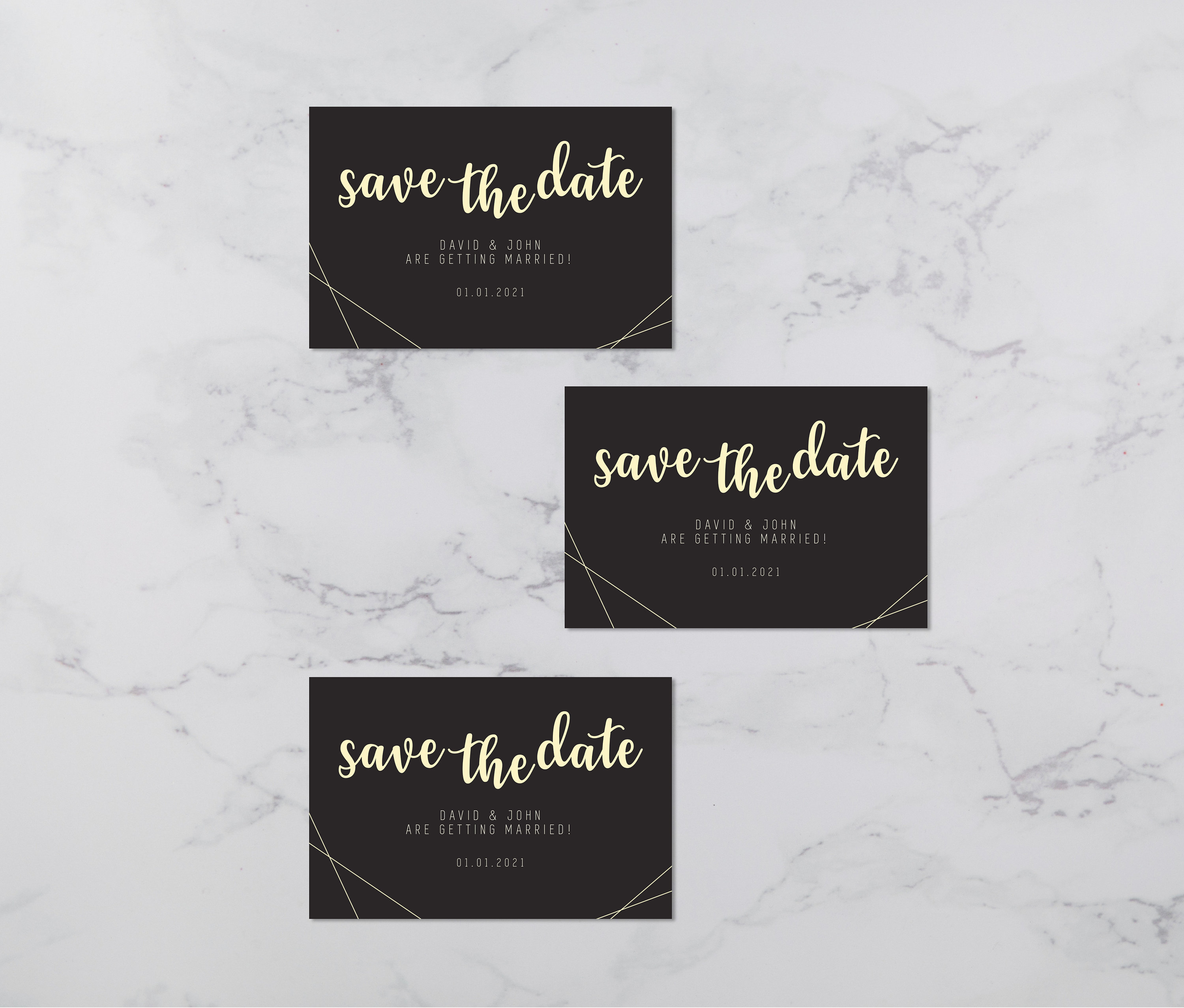 Flat lay photograph of 3 wedding save the date cards and white envelope. The design of each is mostly black card with gold colour details.