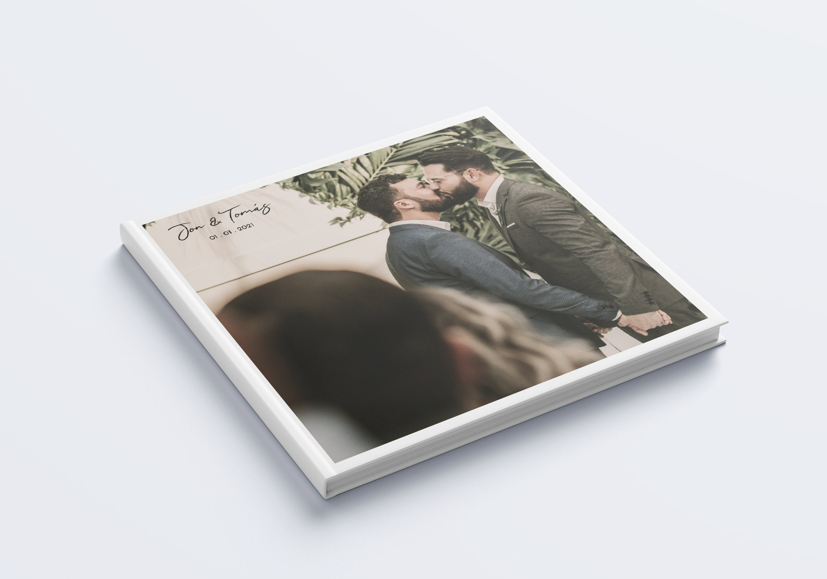 A photograph of a square hardcover book, with a wedding photo printed on the front cover. There is some text overlaying the top left side of the image, with the couples names and wedding date.