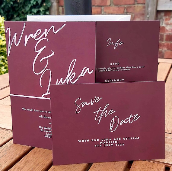 Photograph of a burgundy wedding invitation, information card, save the date and envelope - all standing on a table. Each card is burgundy with a light white/pink calligraphy script.