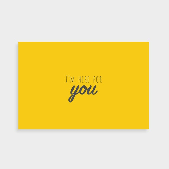 """Bright yellow postcard which says """"Here for you"""" in a dark grey calligraphy font in the middle"""