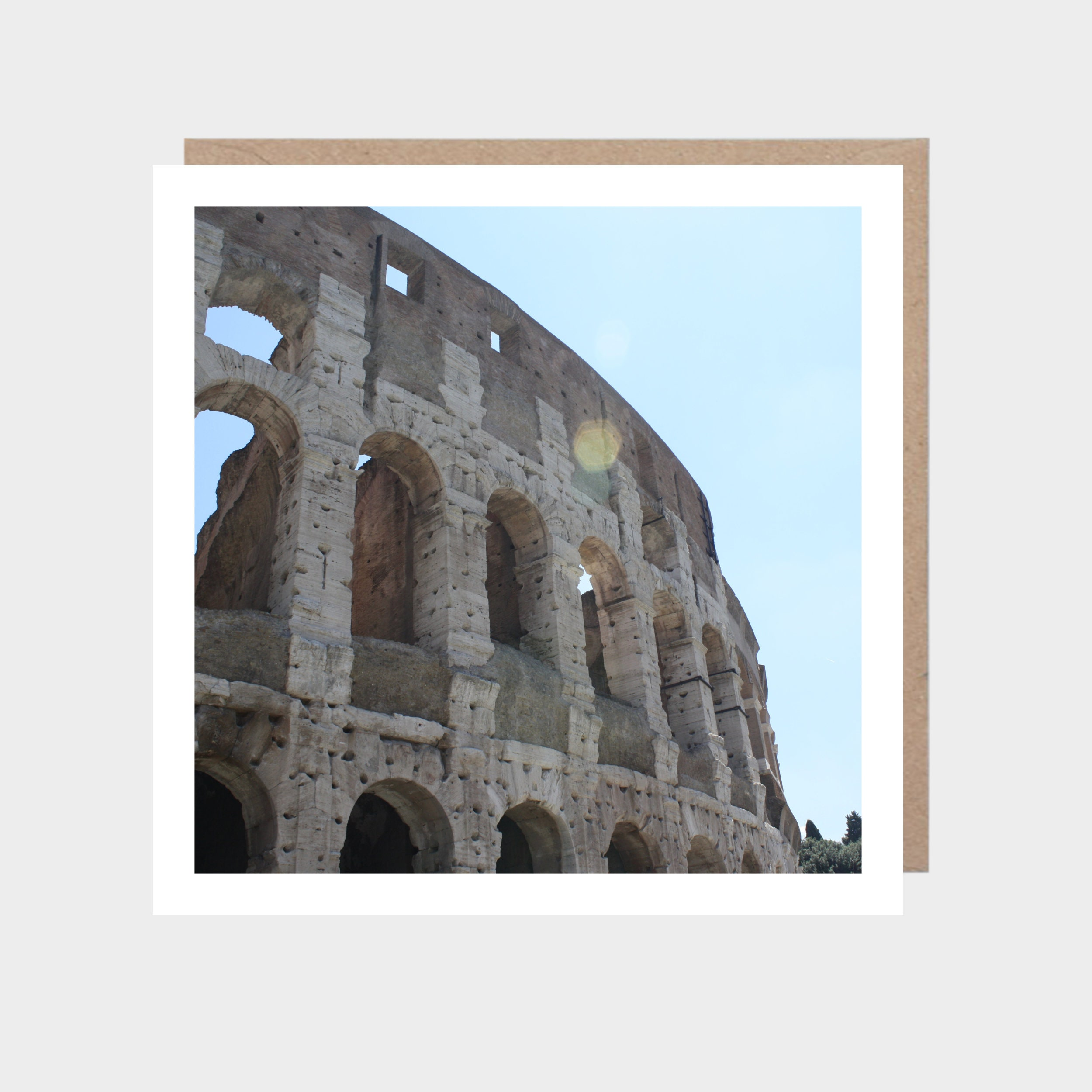 Square card with a close-up photo of the colosseum, with a brown kraft envelope