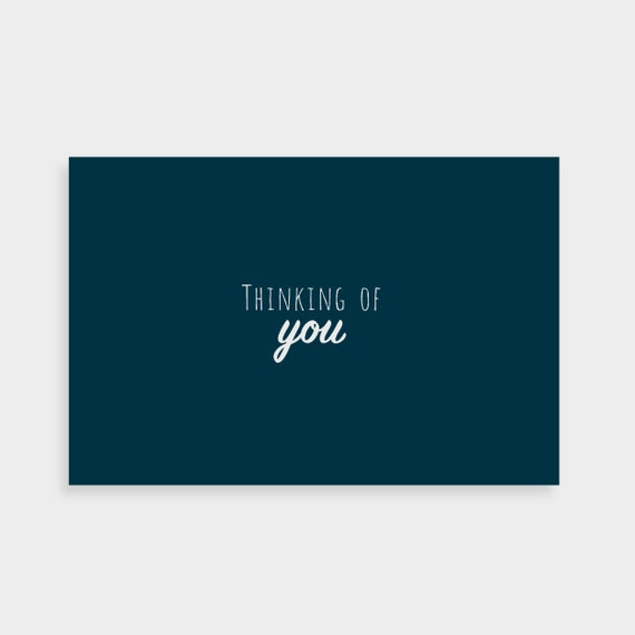 """Dark blue postcard which says """"Thinking of you"""" in a white calligraphy font in the middle"""