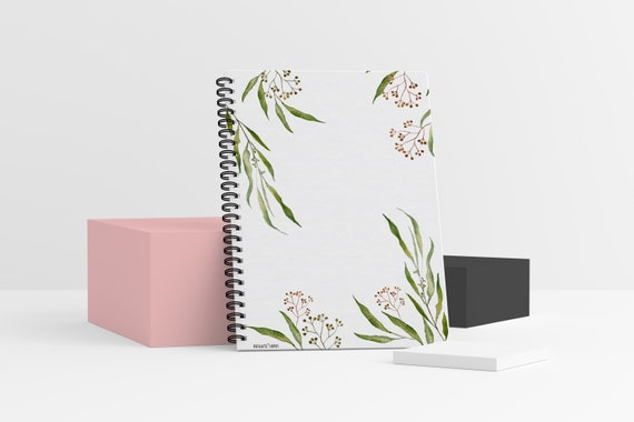A standing spiral-bound notebook with a green leafy design on the front cover