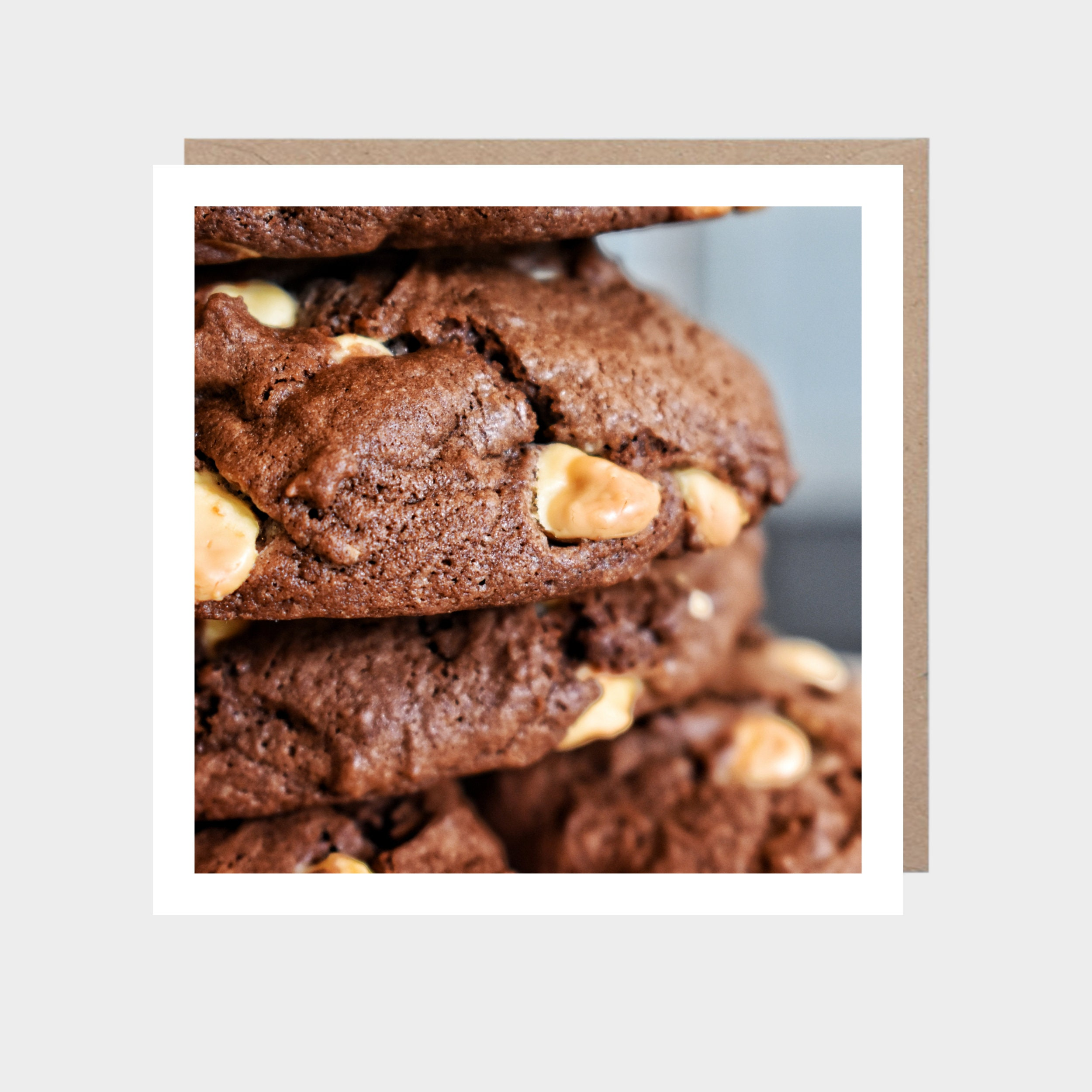 Square card with a close-up photo of chocolate cookies, with a brown kraft envelope