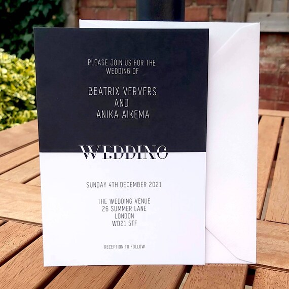 Photograph of a monochrome wedding invitation and white envelope standing on an outside table.