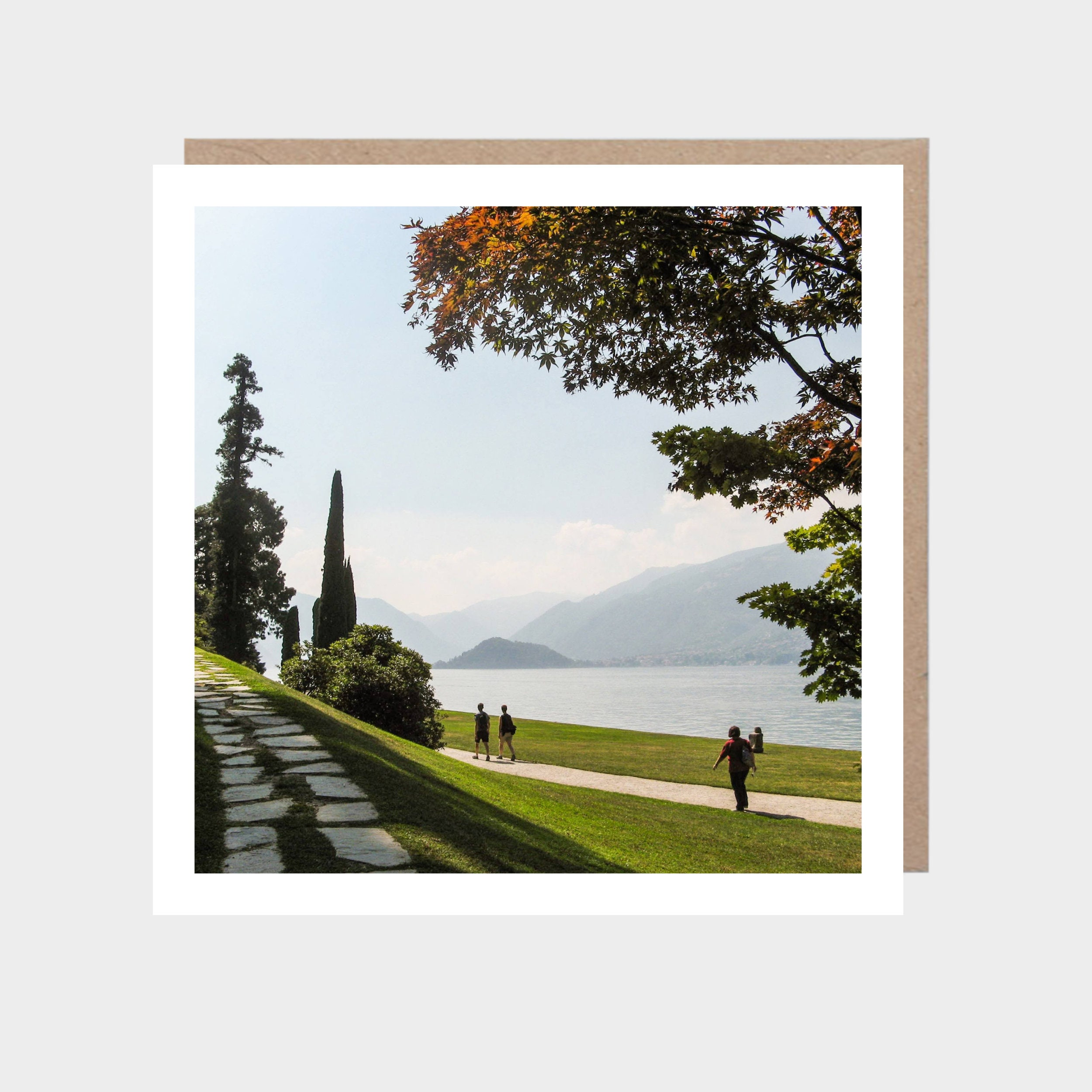Square card with a photo of Lake Como, with a brown kraft envelope