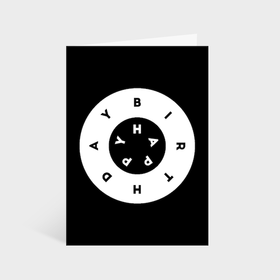 """Standing black card with black and white rings in the centre. Text within the rings says """"Happy Bithday"""""""