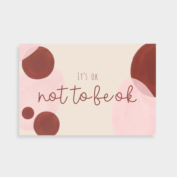 "Cream postcard with overlapping pink and burgundy shapes and abstract line drawings. Postcard says ""It's ok not to be ok"" in the middle."