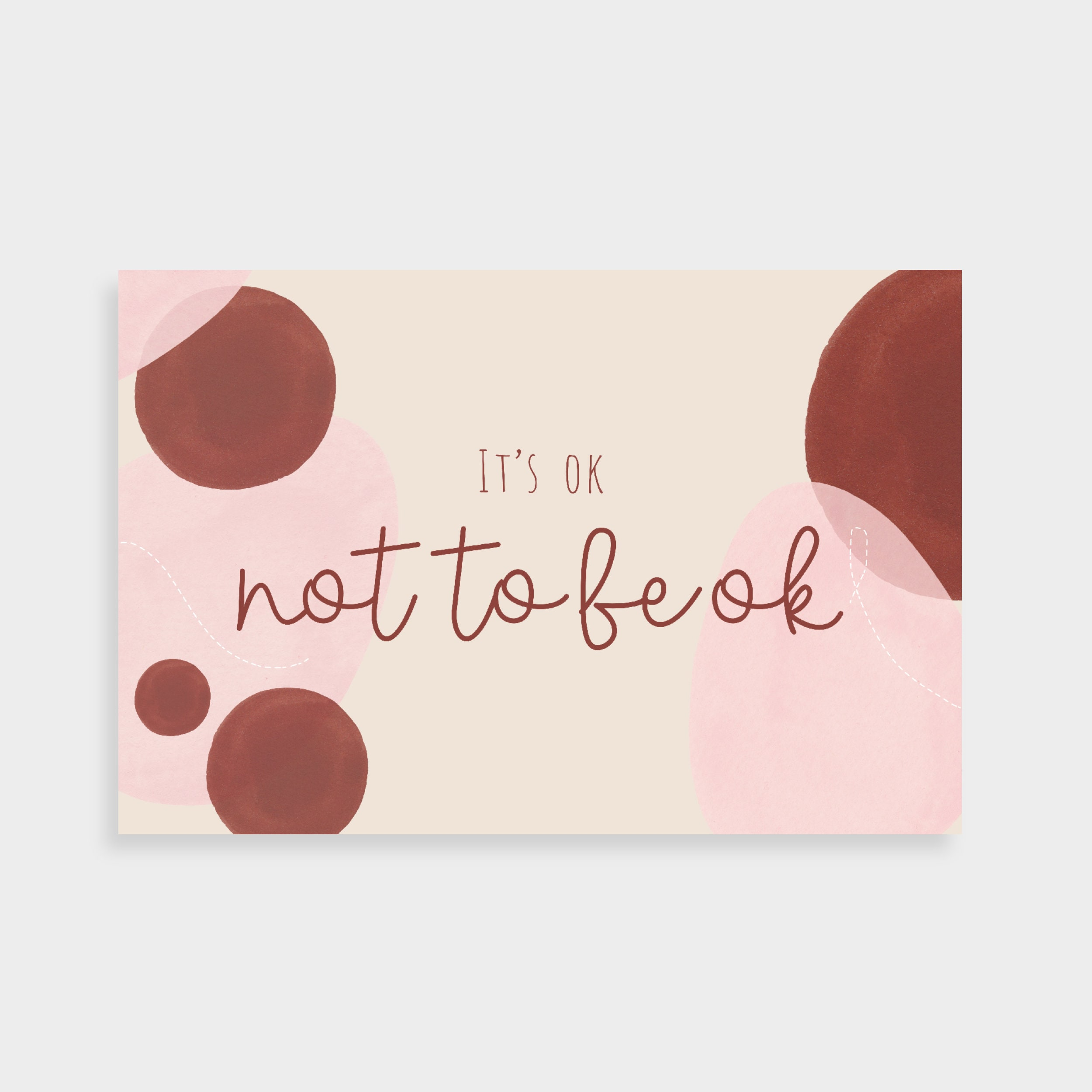 """Cream postcard with overlapping pink and burgundy shapes and abstract line drawings. Postcard says """"It's ok not to be ok"""" in the middle."""