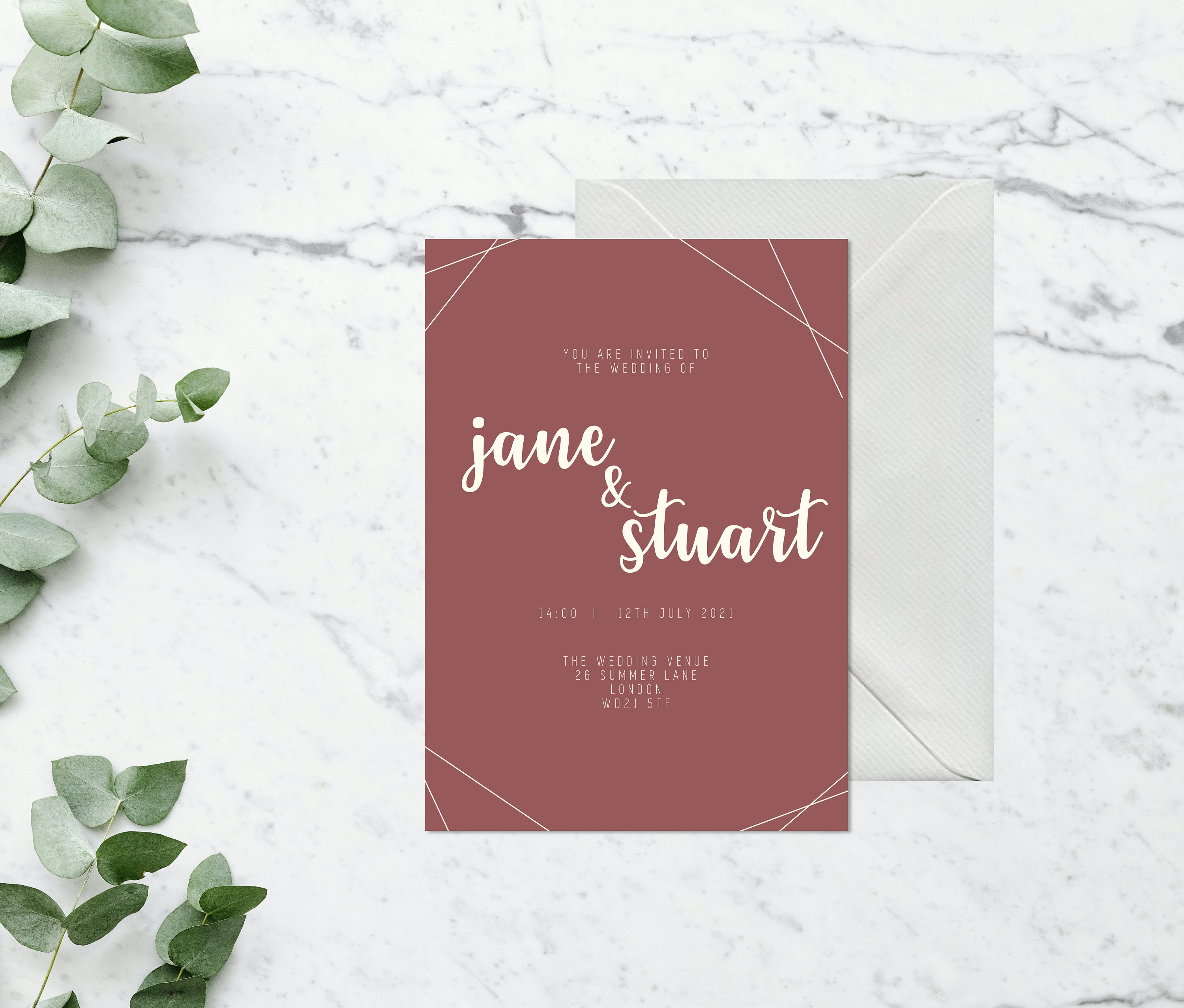 Flat lay photograph of a wedding invitation and white envelope. The design of each is mostly pink card with cream colour details.
