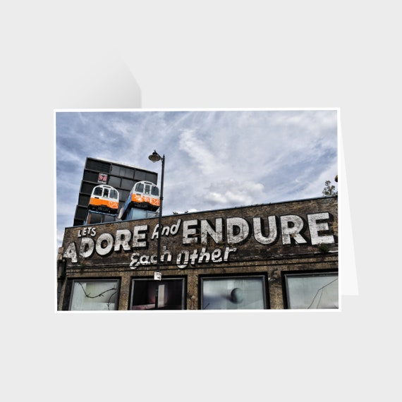 """Standing landscape rectangular card with a photo of London street art which says """"Let's Adore and Endure Each Other"""""""