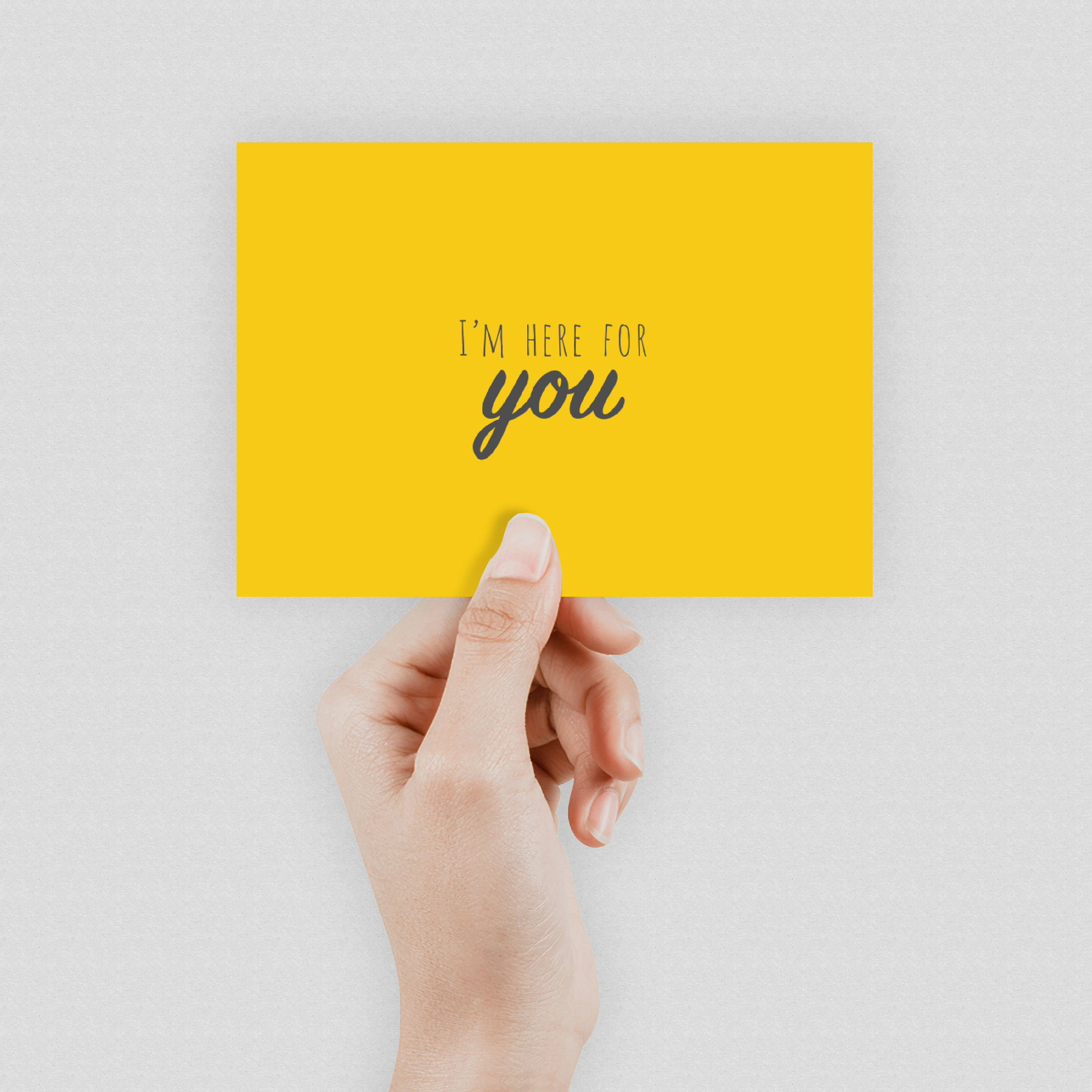 """A hand holding a bright yellow postcard which says """"Here for you"""" in the middle"""