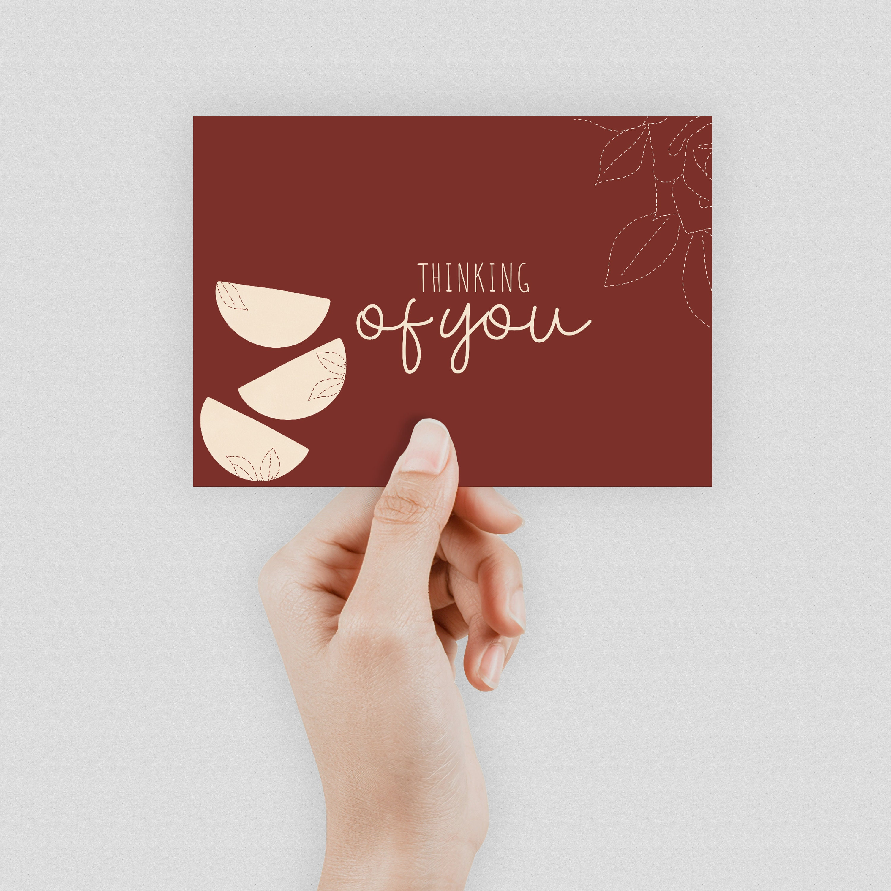 """A hand holding a dark burgundy postcard which says """"Thinking of you"""" in the middle"""