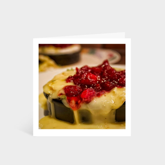 Standing square card with a close-up photo of melting camembert cheese with cranberry sauce on top
