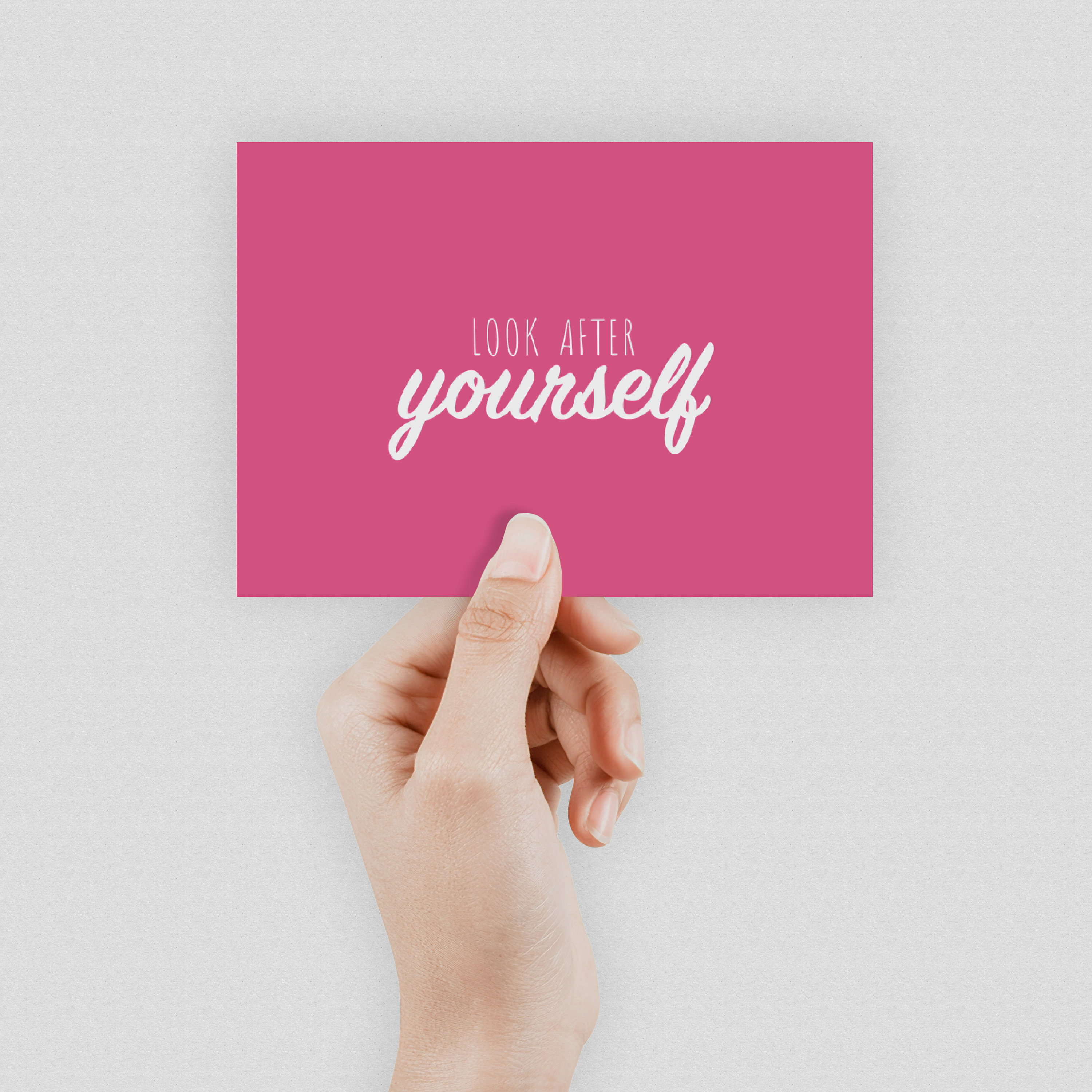 """A hand holding a bright pink postcard which says """"Look after yourself"""" in the middle"""
