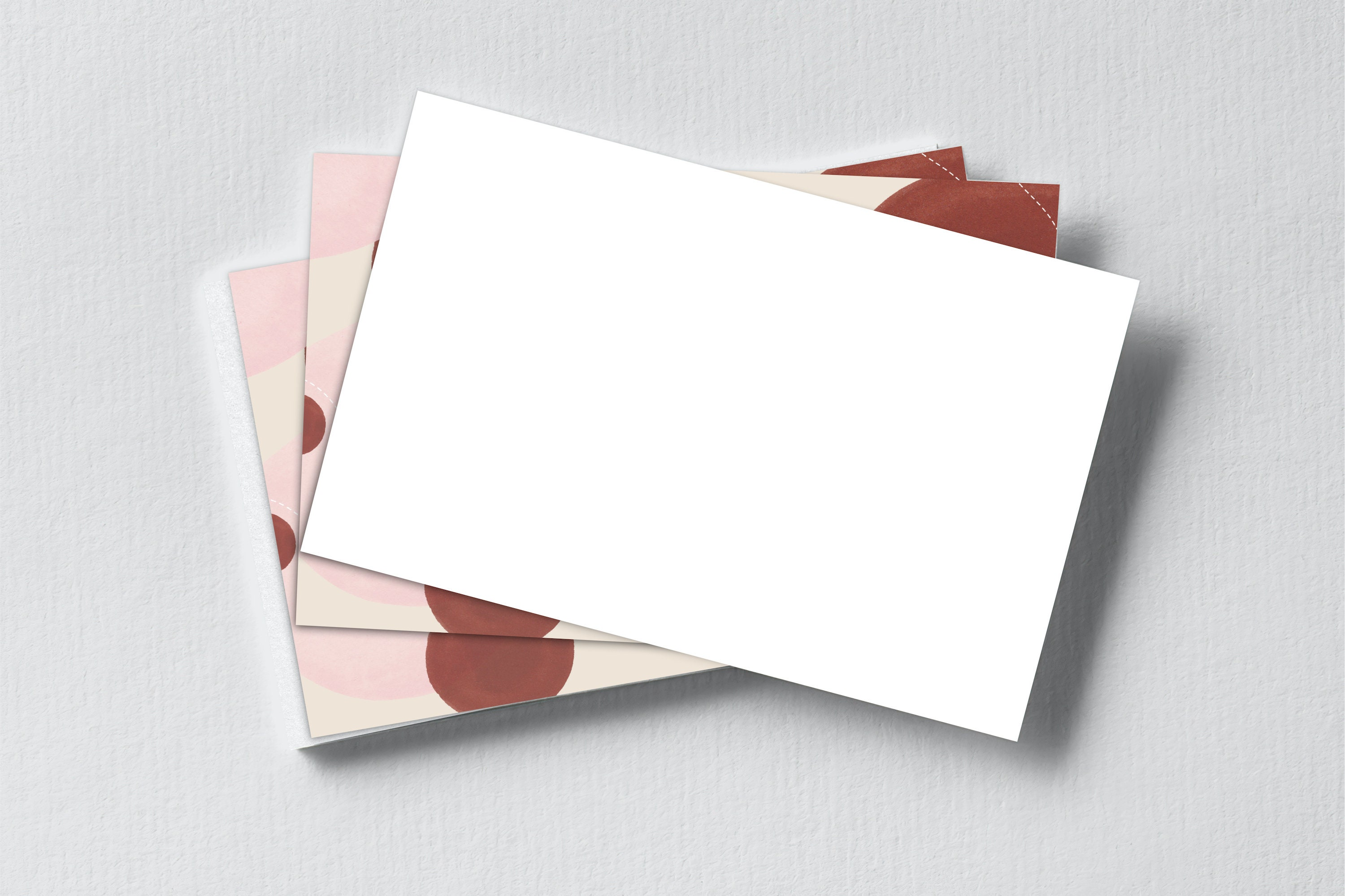 A stack of notecards. The postcard on the top is face down, showing that the back is left completely blank.
