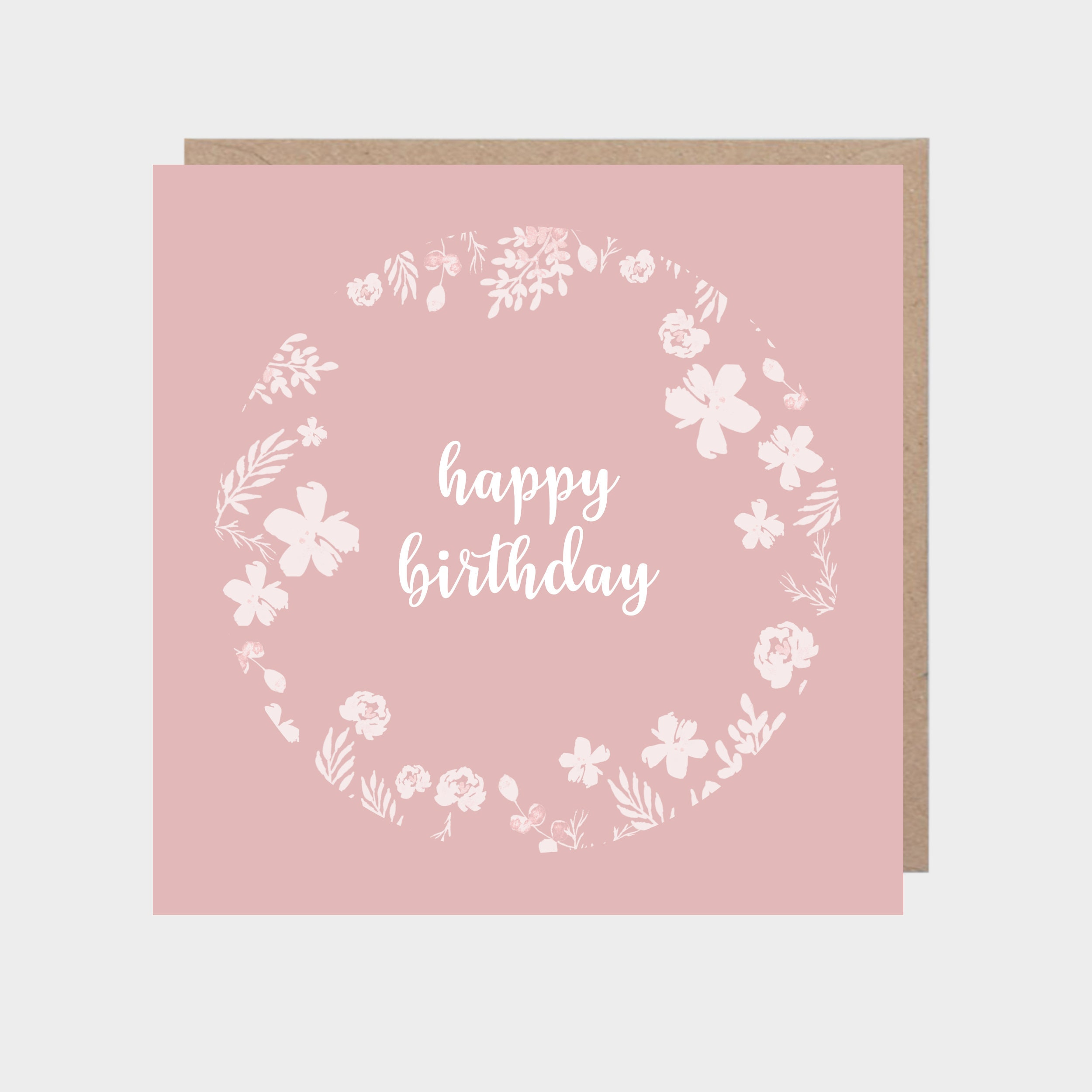 Pink card with illustrated white floral circle, with a brown kraft envelope.
